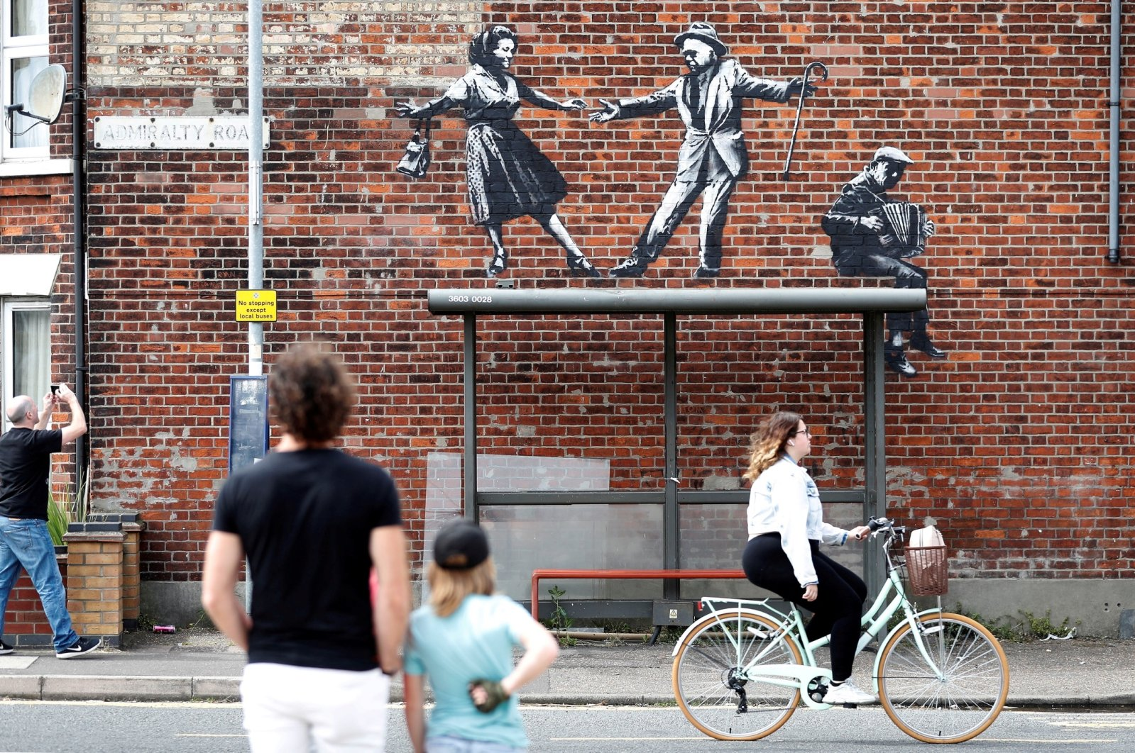 People stop to look at artwork created by Banksy in Great Yarmouth, U.K., Aug. 8, 2021. (Reuters Photo)