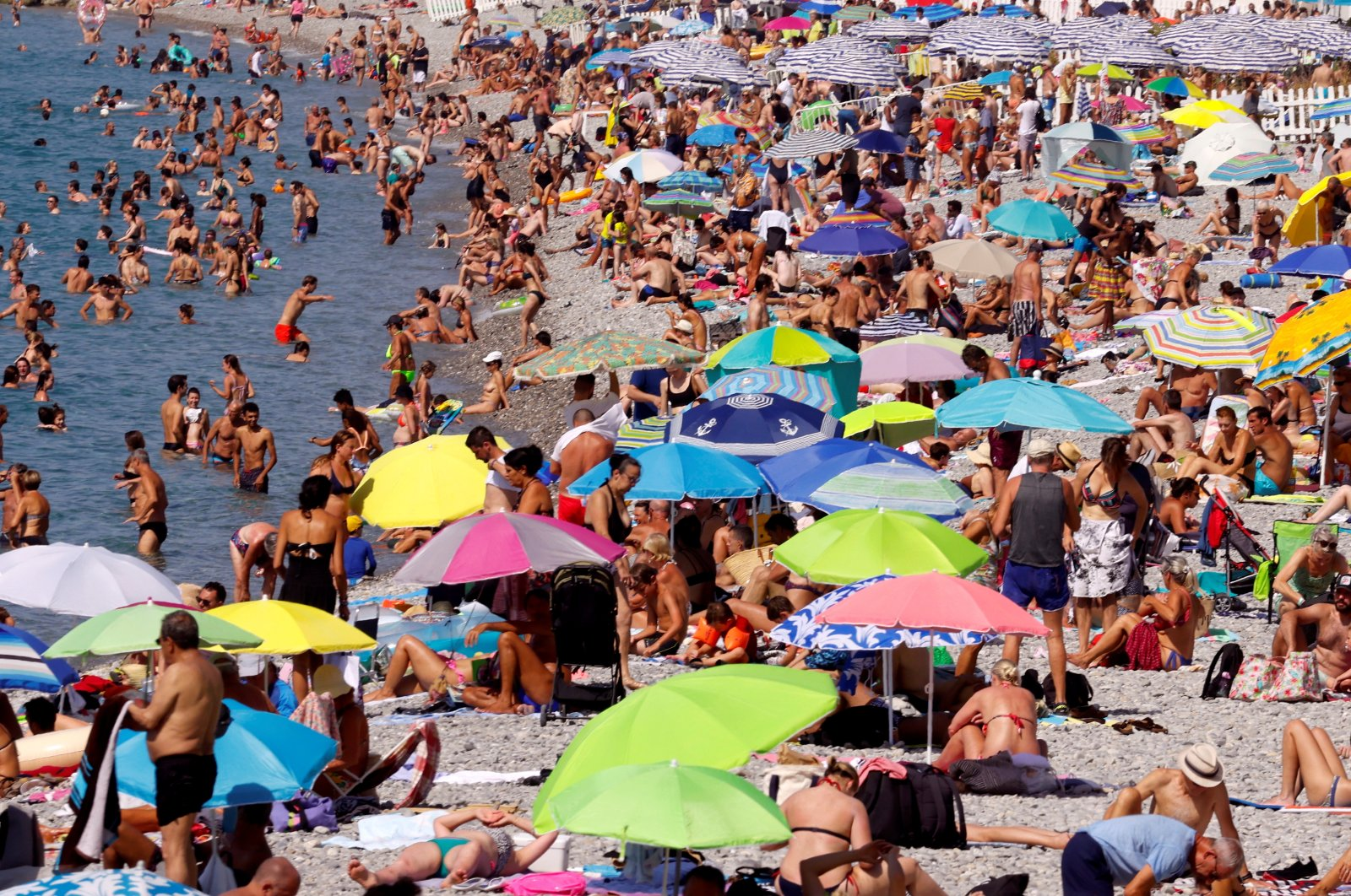 People enjoy a warm and sunny day on the beach of the Promenade des Anglais in Nice, Aug. 14, 2021. (Reuters Photo)