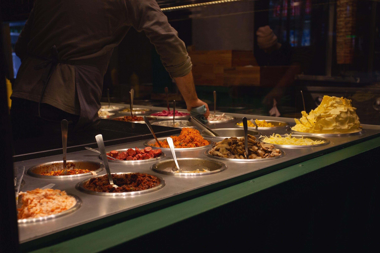 Turkish people in cafe prepare kumpir. (Shutterstock Photo)