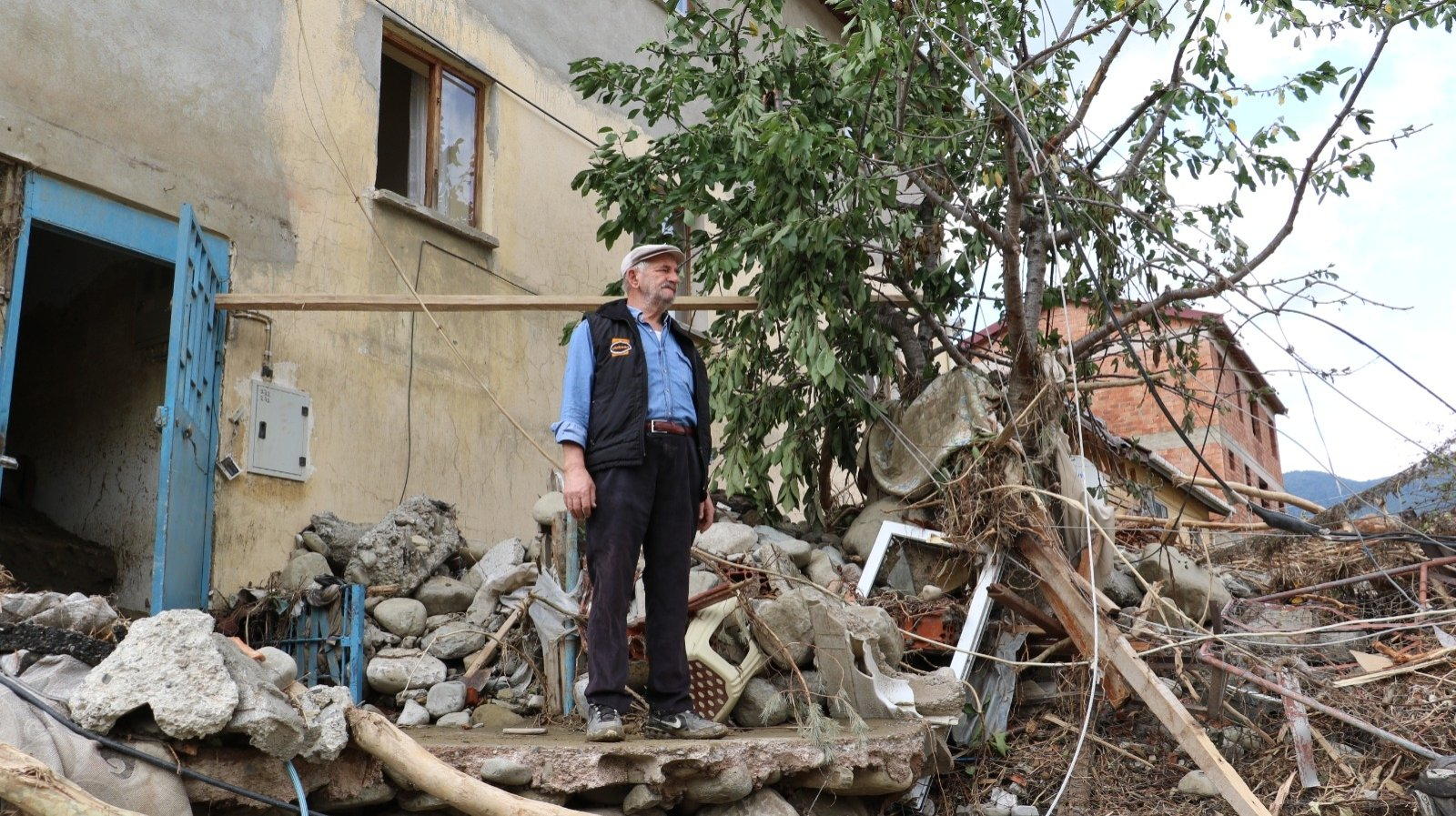 A man stands among debris outside his home in Babaçay, in Sinop, northern Turkey, Aug. 15, 2021. (DHA PHOTO)