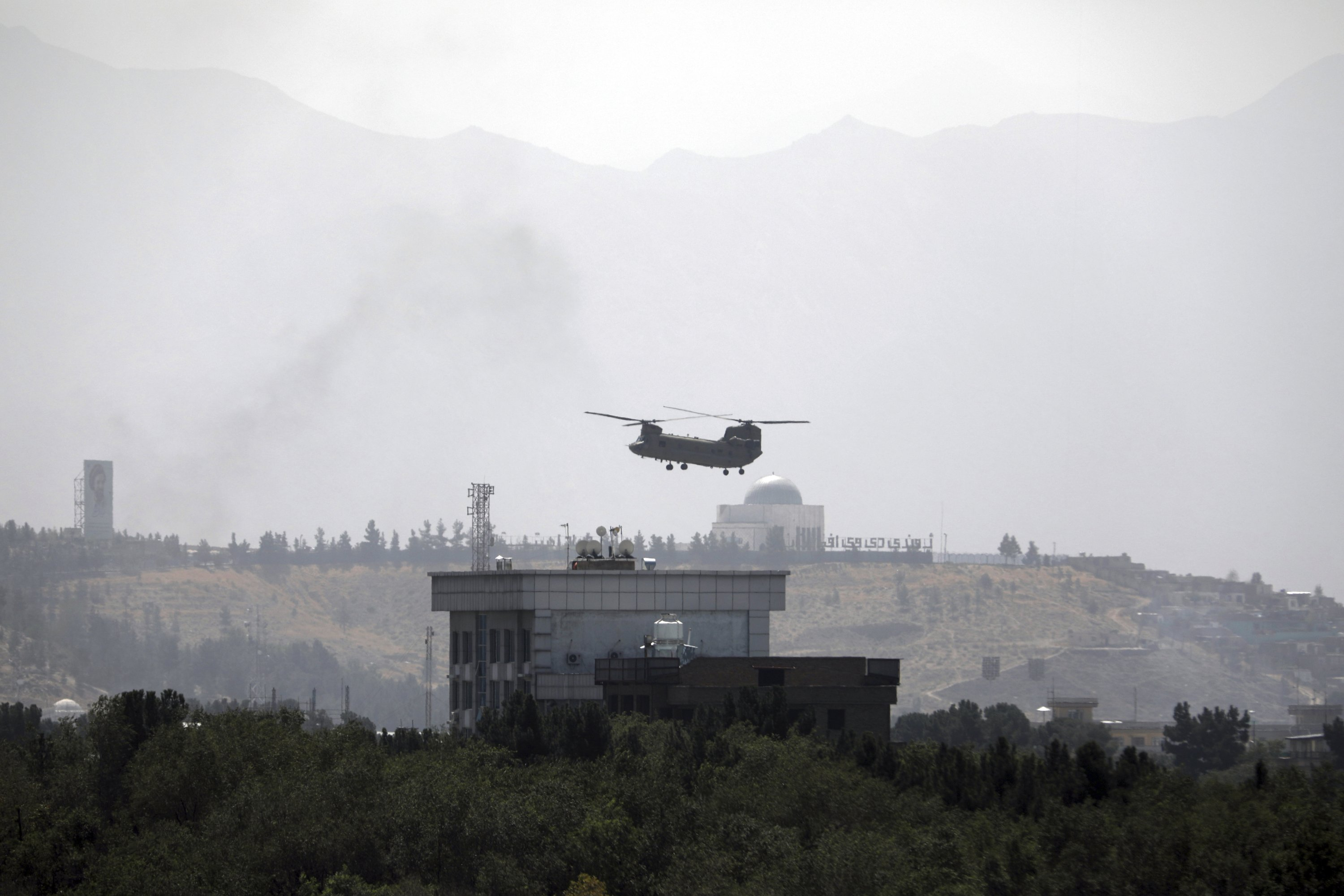 A U.S. Chinook helicopter flies over the U.S. Embassy in Kabul, Afghanistan, Aug. 15, 2021. Helicopters are landing at the U.S. Embassy in Kabul as diplomatic vehicles leave the compound amid the Taliban advanced on the Afghan capital. (AP Photo)