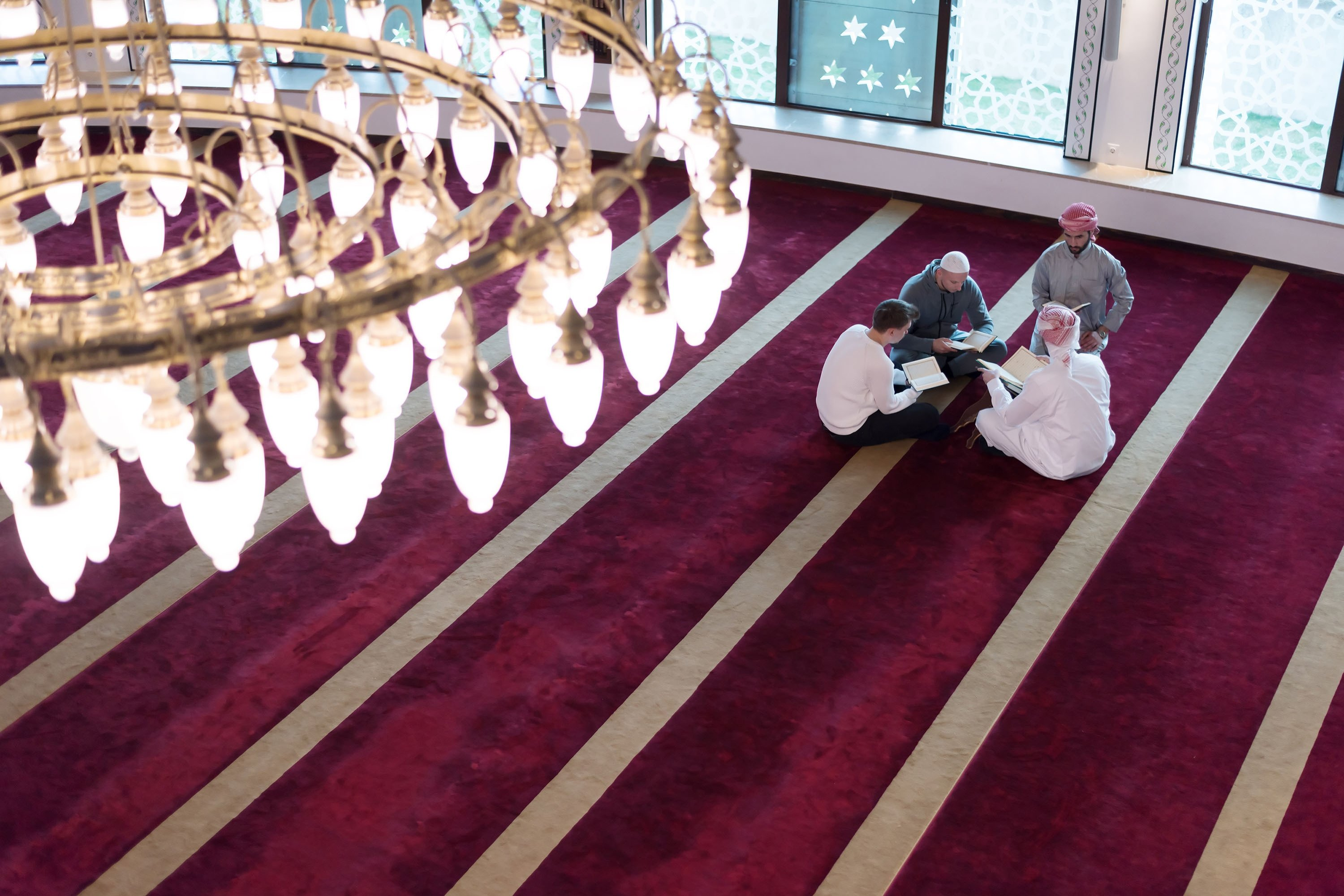 A group of people read the Quran, the holy book of Islam, inside a mosque. (Shutterstock Photo)