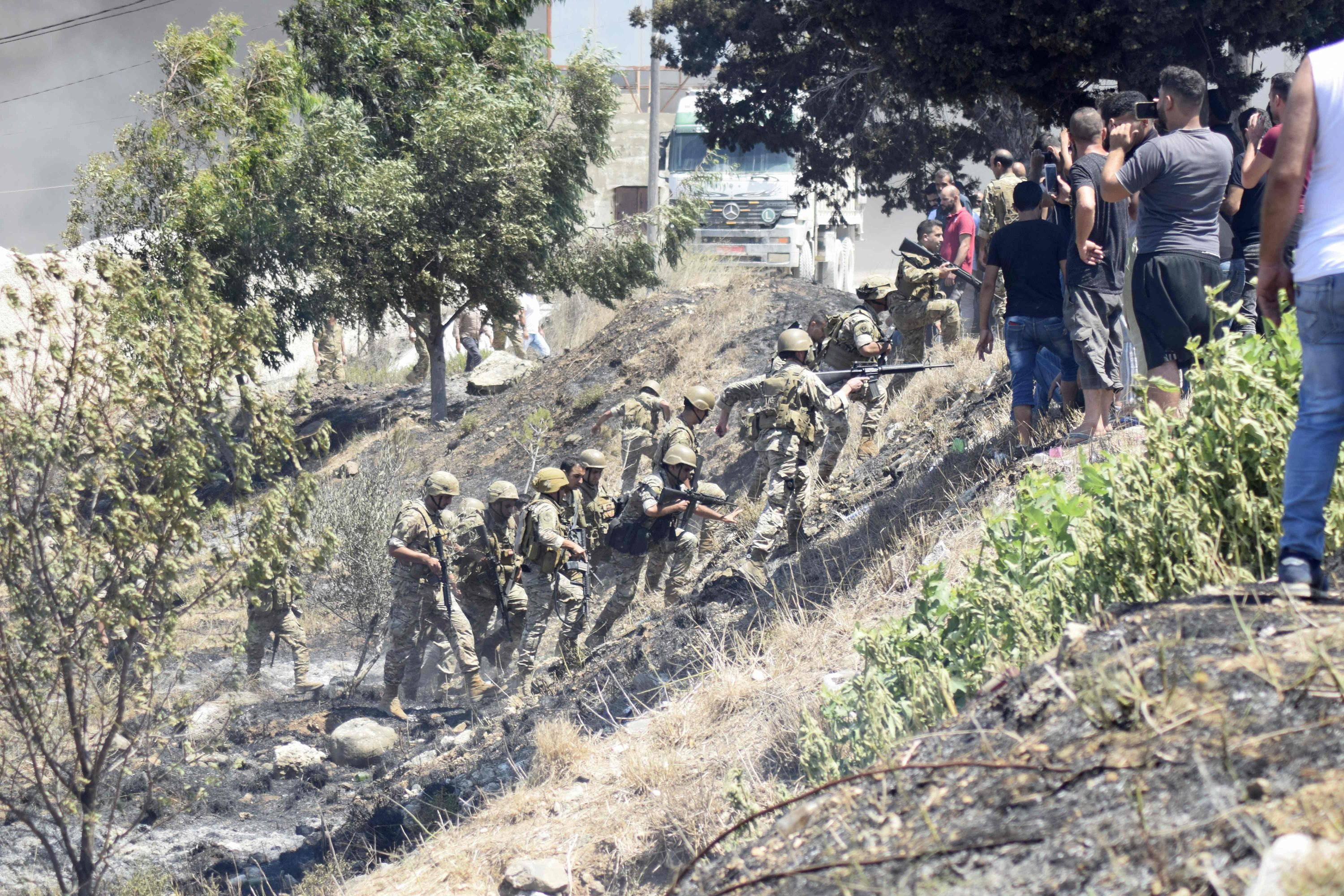 Lebanese army soldiers evacuate the area surrounding the reported home of the lot owner, where the exploded fuel tank was placed, after it was set ablaze by angry locals in the village of Tlel in Lebanon's northern region of Akkar, Aug. 15, 2021. (AFP Photo)