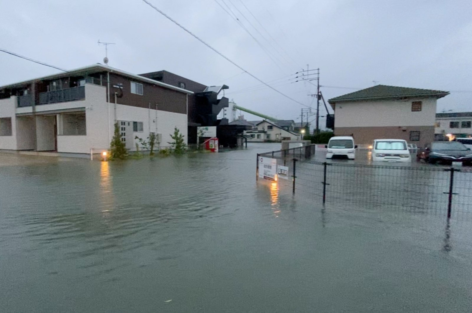 A person stands at a flooded street during heavy rain in Kurume, Fukuoka Prefecture, Japan August 14, 2021, in this still image taken from video provided on social media. (Photo courtesy of @Napspans on Twitter / via Reuters)
