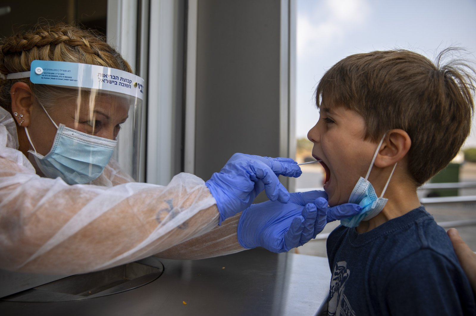 A health worker collects a swab sample from a kid to test for COVID-19 at a testing center, in Tel Aviv, Israel, Aug. 9, 2021. (AP Photo)