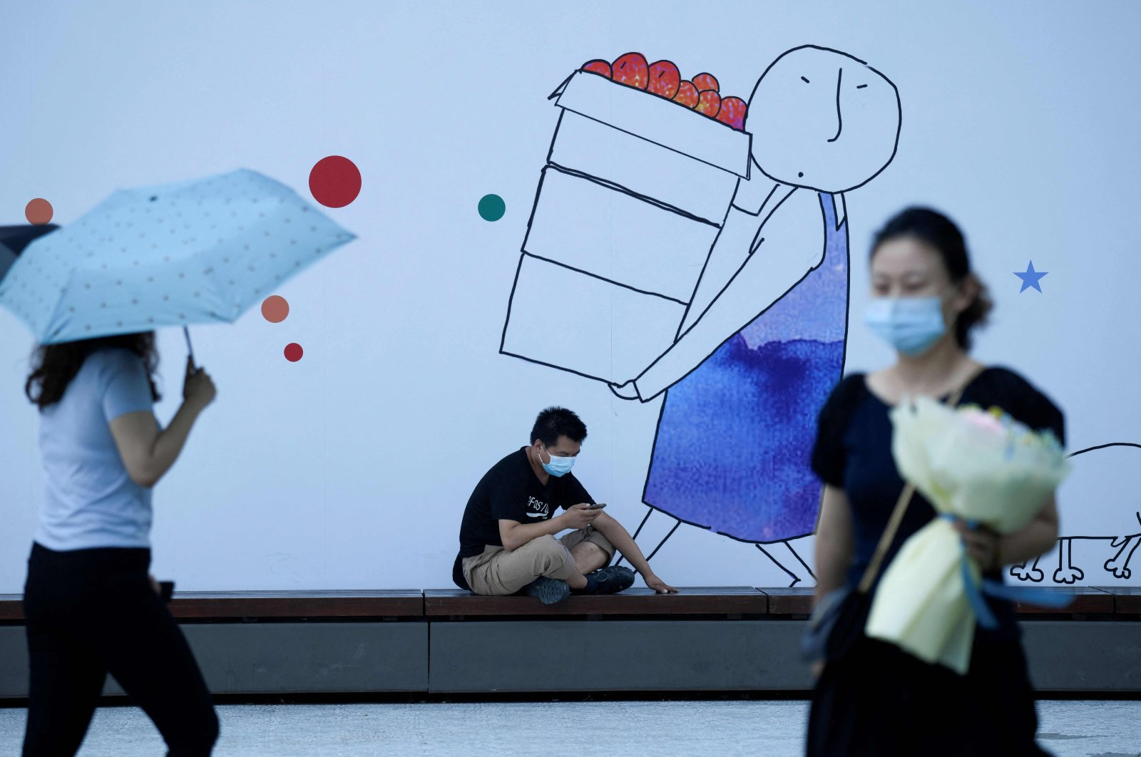 A man wearing a face mask uses his mobile phone in front of an advertisement in Beijing, China, Aug. 11, 2020. (AFP Photo)