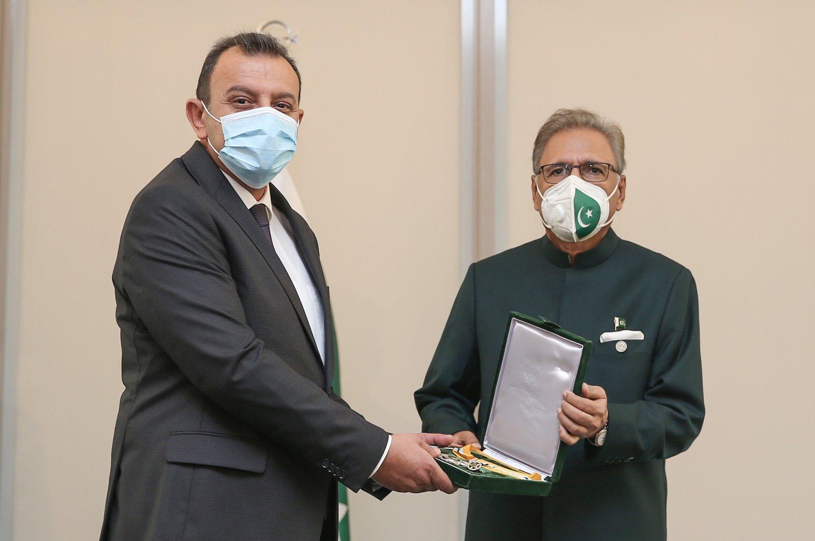 Dr. Selami Kılıç (L) receives his award from Pakistani President Arif Alvi, in Istanbul, Turkey, Aug. 15, 2021. (AA PHOTO)