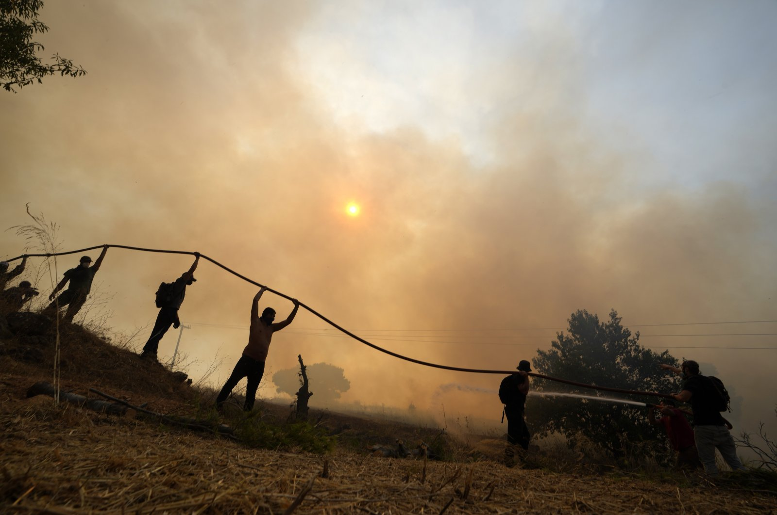 A firefighter tries to extinguish a fire as volunteers hold the water hose during a wildfire in Agios Stefanos, in northern Athens, Greece, Aug. 6, 2021. (AP File Photo)
