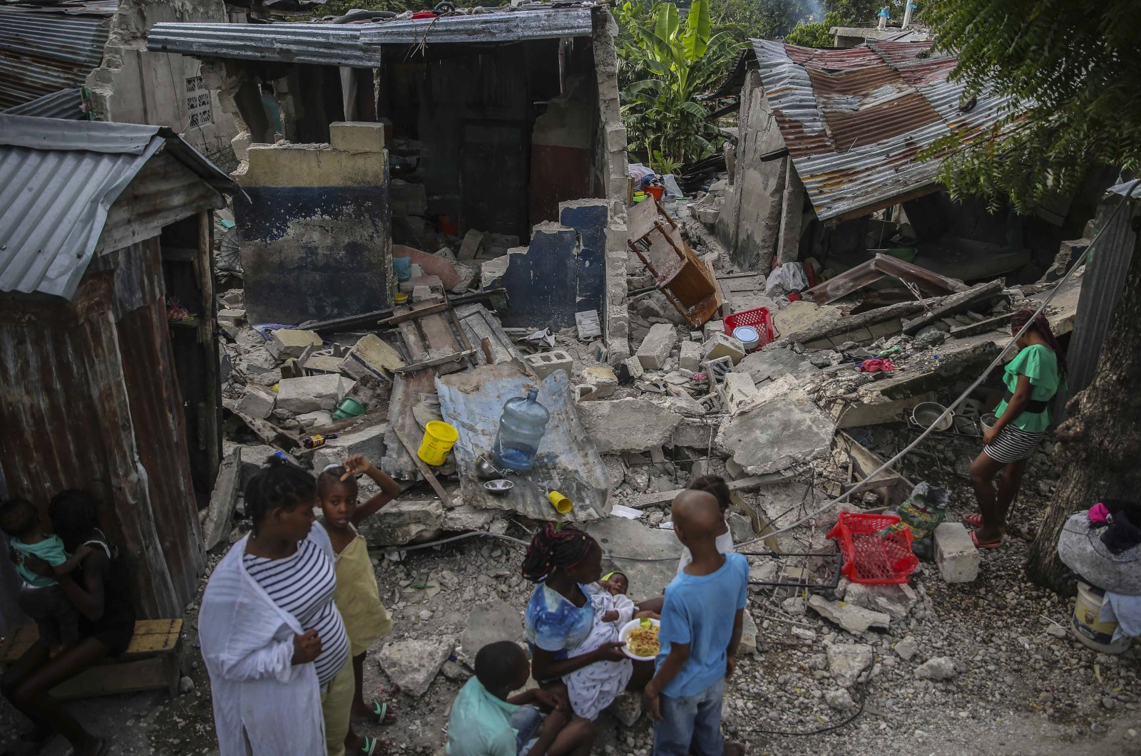 A family eats breakfast in front of homes destroyed by a 7.2 magnitude earthquake in Les Cayes, Haiti, Sunday, Aug. 15, 2021. (AP Photo)