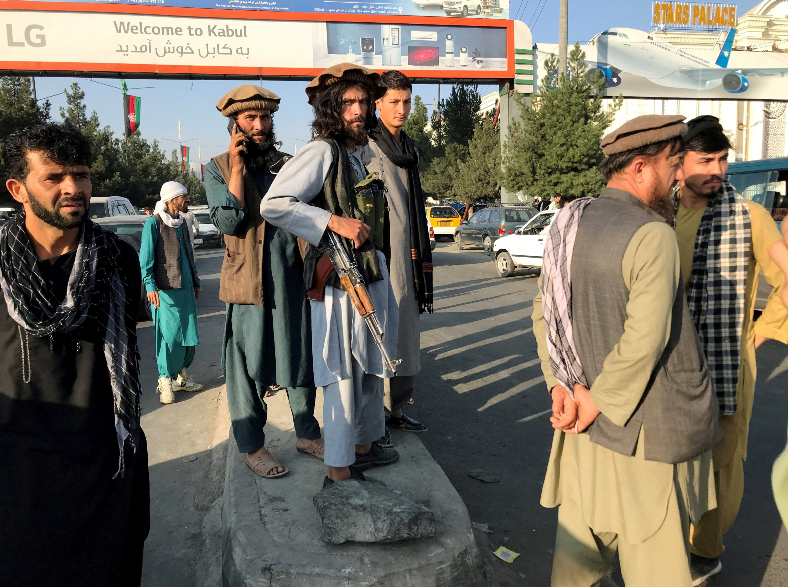 A Taliban member (C) stands outside Kabul Hamid Karzai International Airport in Kabul, Afghanistan, Aug. 16, 2021. (Reuters Photo)