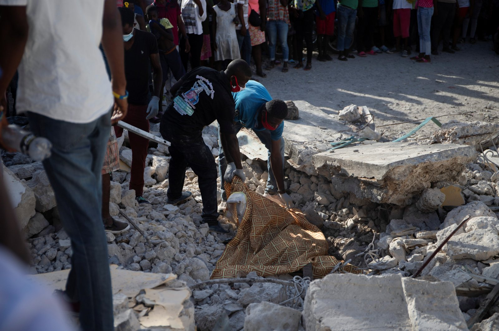 People cover the body of a person lying on the debris with a sheet, after a 7.2 magnitude earthquake, in Les Cayes, Haiti, Aug. 15, 2021. (Reuters Photo)