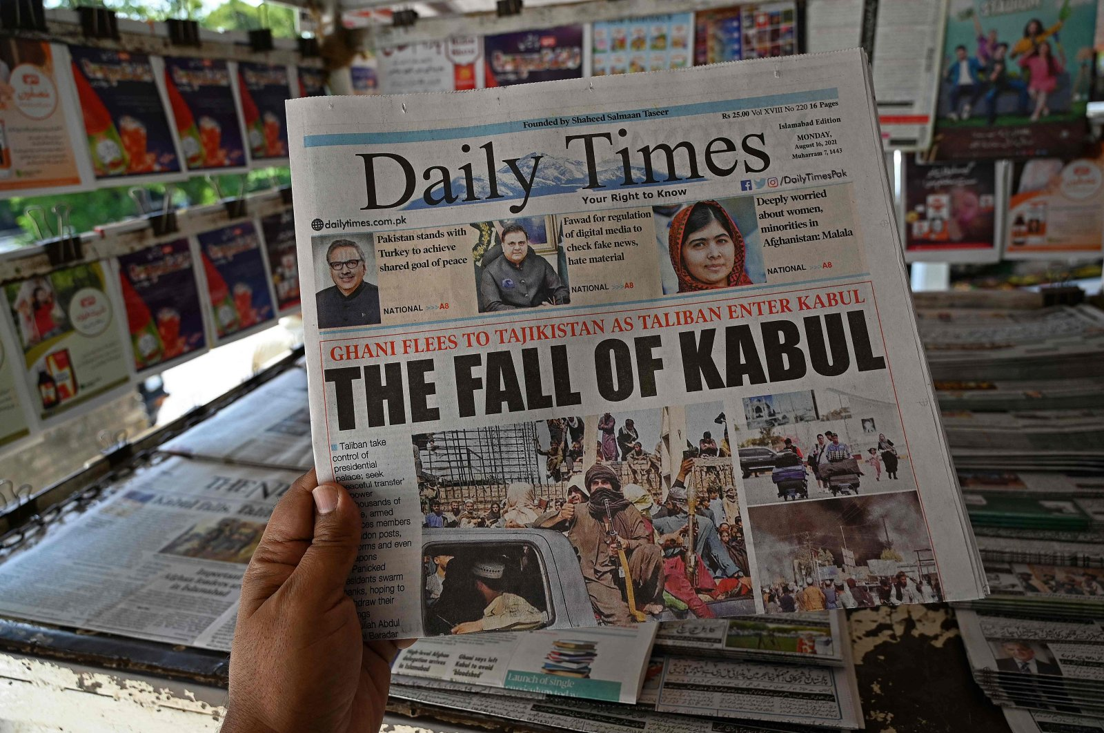 A man holds a newspaper displaying front page news about Afghanistan, at a stall in Islamabad, Pakistan, Aug. 16, 2021. (AFP Photo)