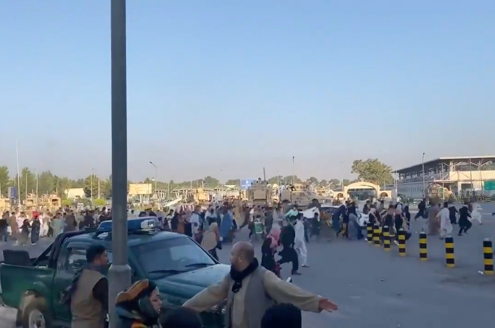 In this still image taken from social media, a horde of people run towards the Kabul Hamid Karzai Internation Airport terminal, after Taliban insurgents took control of the presidential palace in Kabul, Afghanistan, Aug. 16, 2021. (Jawad Sukhanyar via Reuters)
