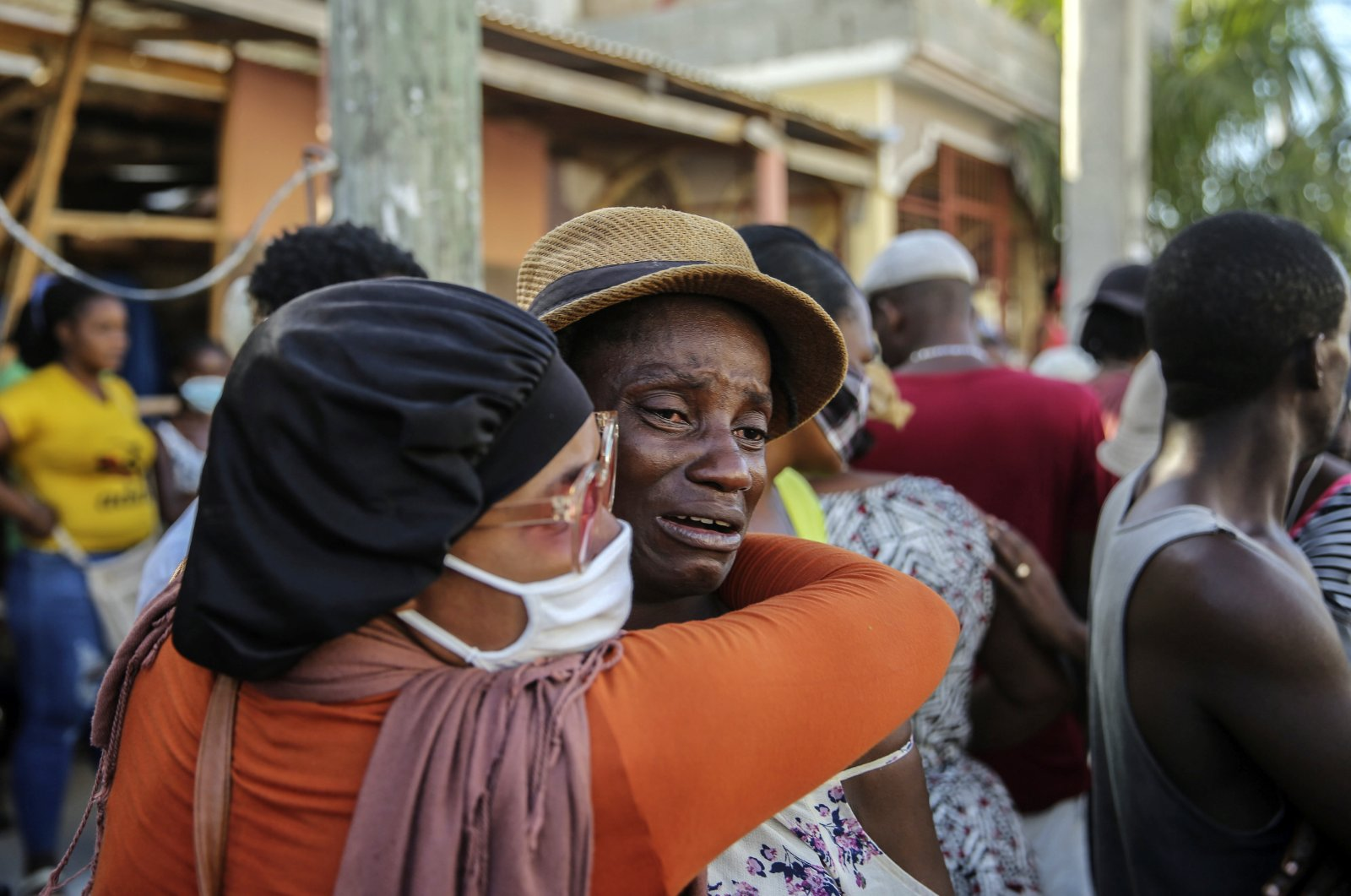 People cry during the search for those who are still missing in a house destroyed by the earthquake in Les Cayes, Haiti, Sunday, Aug. 15, 2021.  (AP Photo)