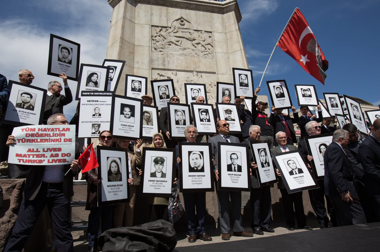 """A retired diplomat holds a placard reading """"All lives matters, as do Turks lives,"""" among others with portraits of victims of Armenian terrorist attacks in front of Atatürk Monument in Ulus Square, Ankara, Turkey, on April 4, 2015. (Getty Images Photo)"""