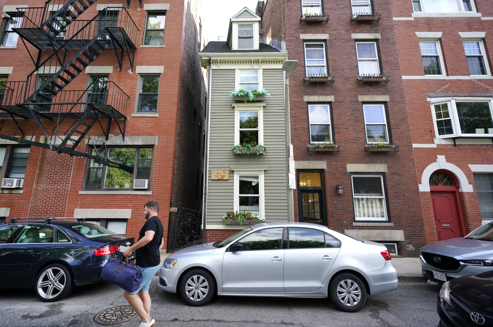 A man walks by Boston's famous Skinny House, middle, Aug. 13, 2021, which is on the market for $1.2 million. (AP Photo)