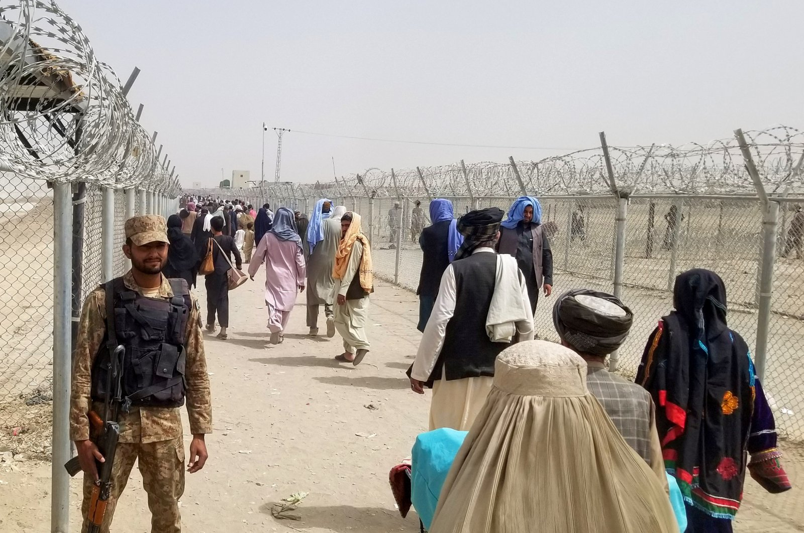 A soldier from the Pakistan Army stands guard as people arriving from Afghanistan make their way at the Friendship Gate crossing point in the Pakistan-Afghanistan border town of Chaman, Pakistan, Aug. 16, 2021. (REUTERS Photo)