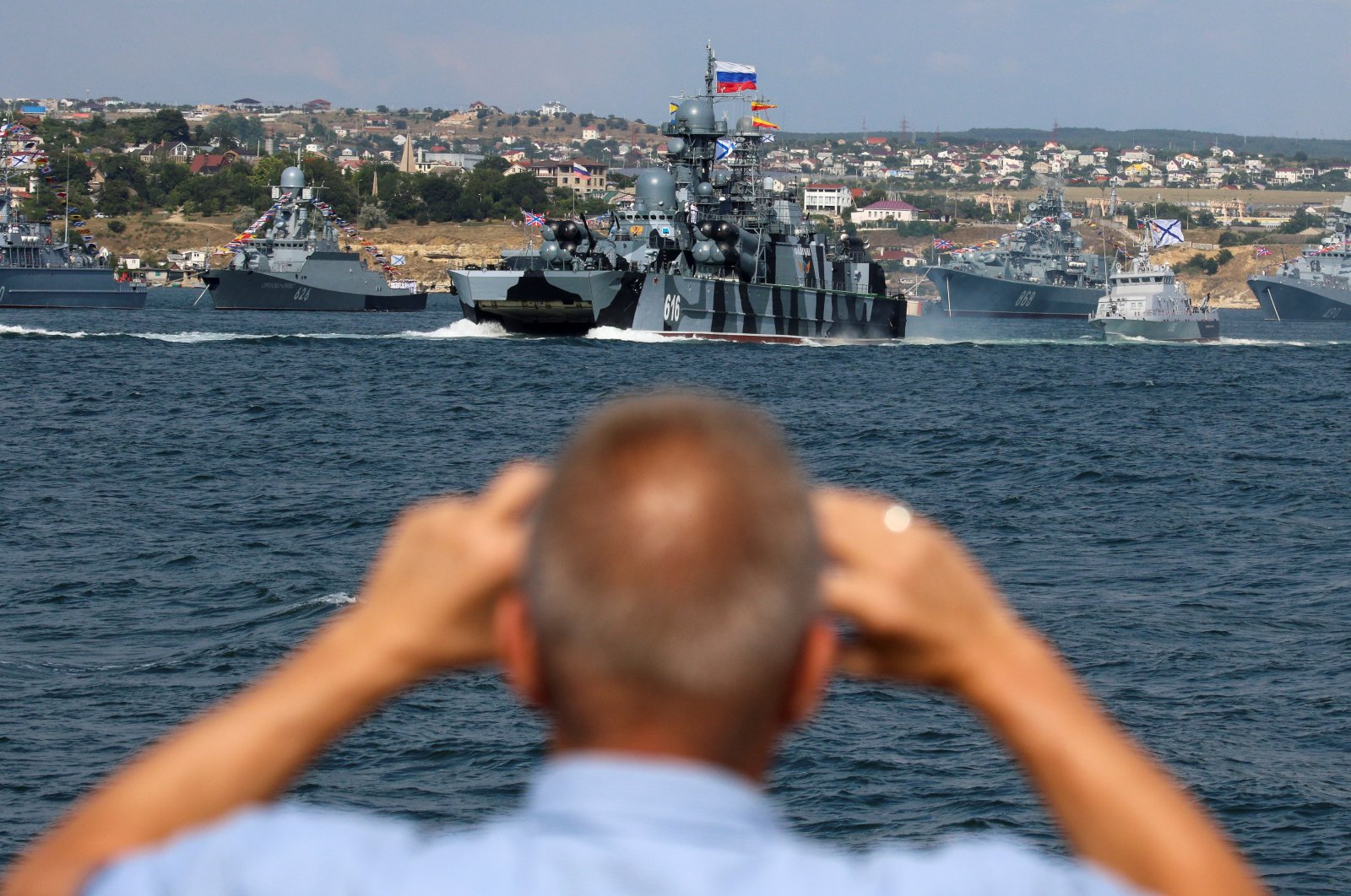 A man films the Russian Navy's warships ahead of the Navy Day parade in the Black Sea port of Sevastopol, occupied Crimea, July 23, 2021. (REUTERS Photo)