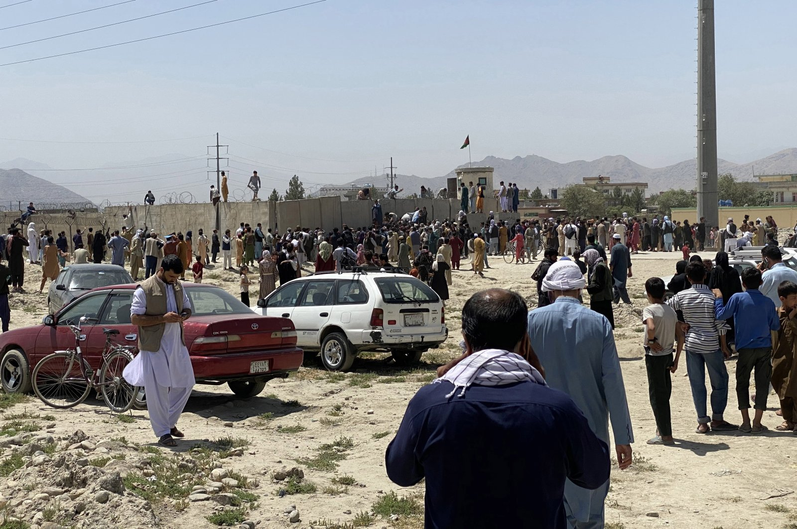People struggle to cross the boundary wall of Kabul Hamid Karzai International Airport in a bid to flee the country after the Taliban took control of Kabul, Afghanistan, Aug. 16, 2021. (EPA Photo)