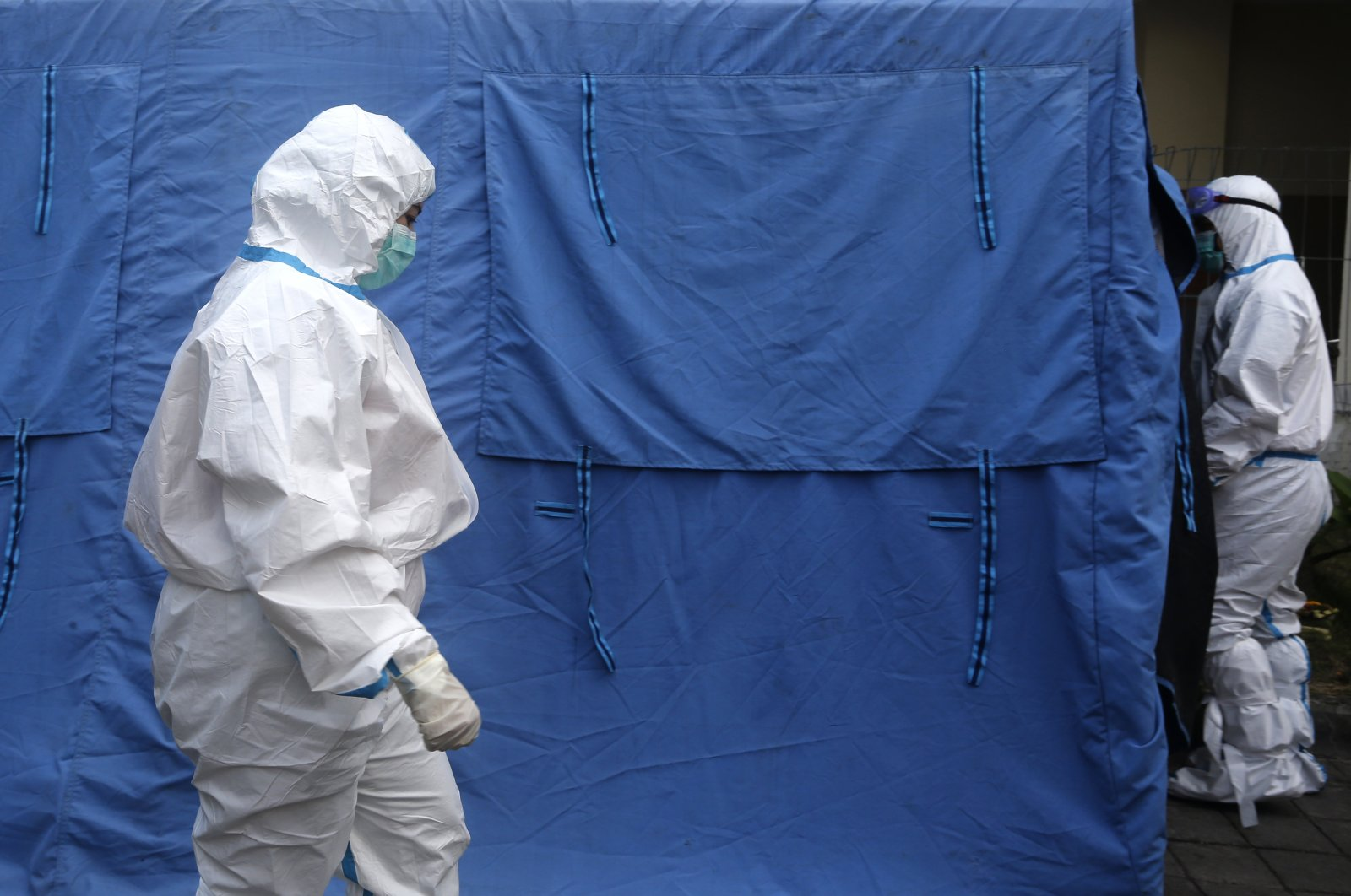 Workers in protective suits walk into a tent to pick up the body of a COVID-19 victim to take for cremation in Bali, Indonesia, Aug. 16, 2021. (AP Photo)