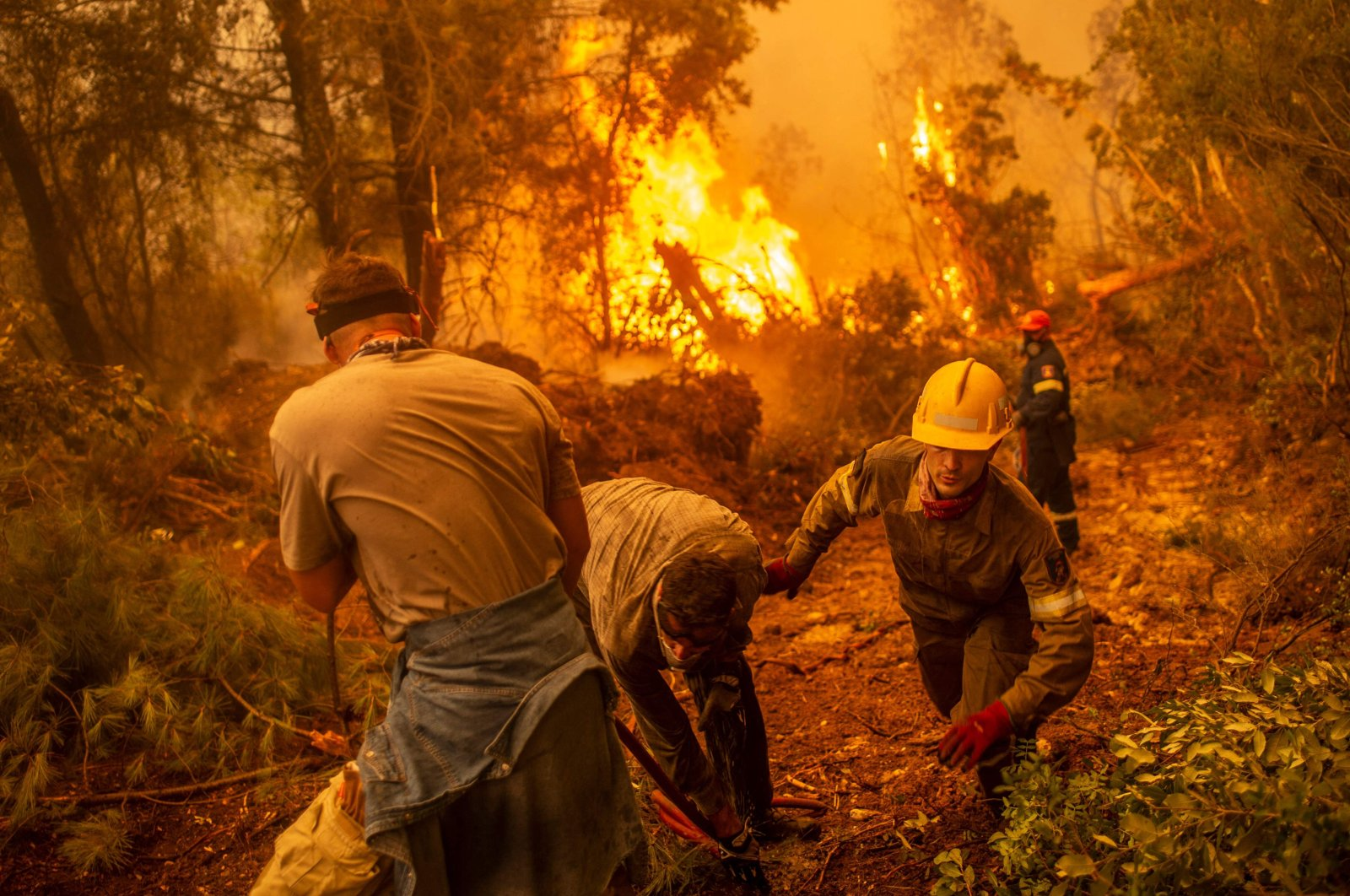 Firefighters and volunteers use a water hose near a burning blaze trying to extinguish a fire in the village of Glatsona on Evia (Euboea) island, Greece, August 9, 2021. (AFP Photo)