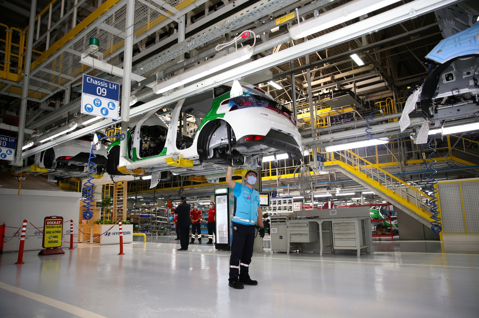 An employee looks up at a Hyundai i20 car being manufactured in Kocaeli province, northwestern Turkey, Aug. 28, 2020. (AA Photo)