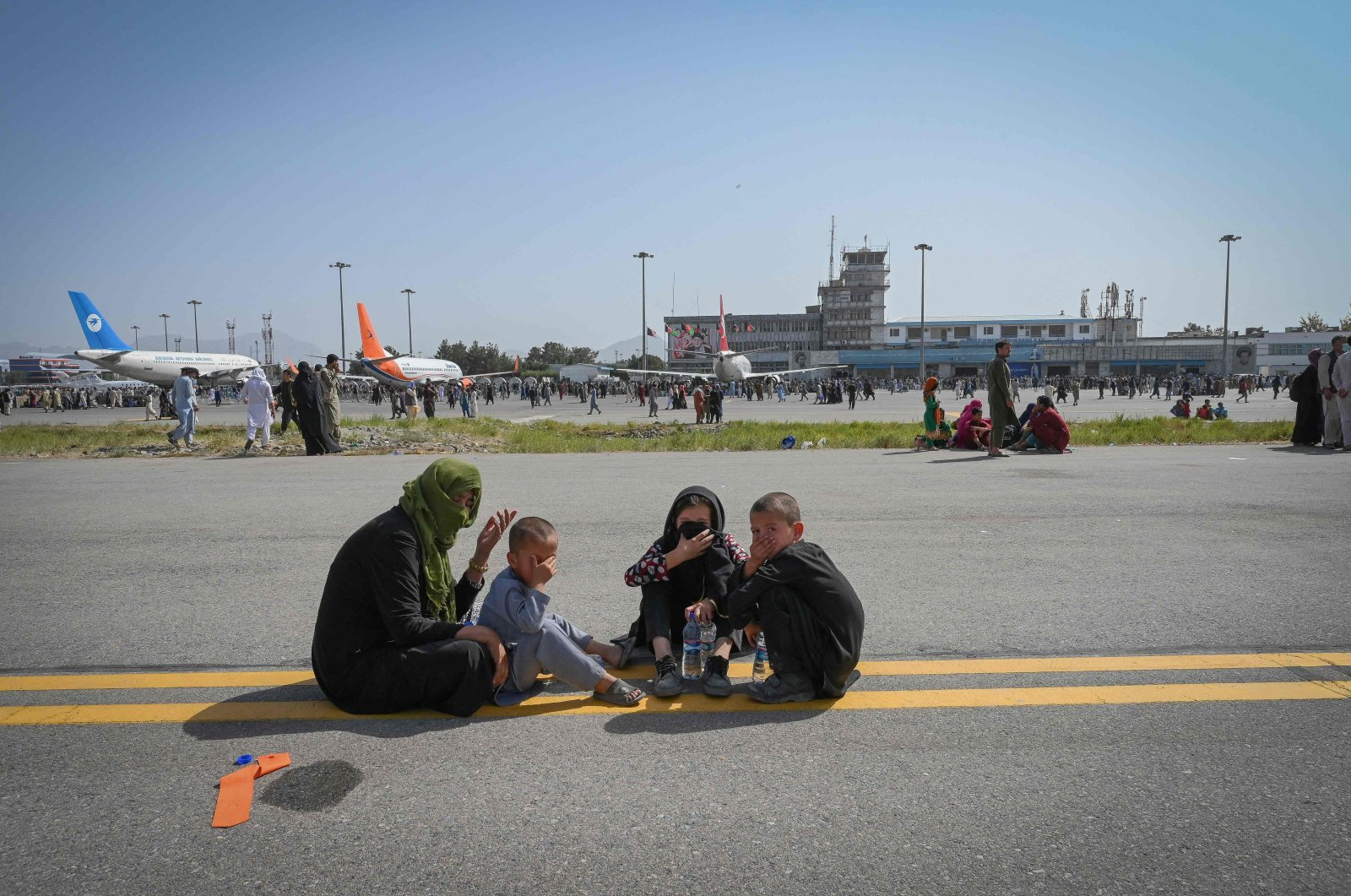 Afghan people sit along the tarmac as they wait to leave the Kabul Hamid Karzai International Airport in Kabul, Afghanistan on Aug. 16, 2021. (AFP Photo)