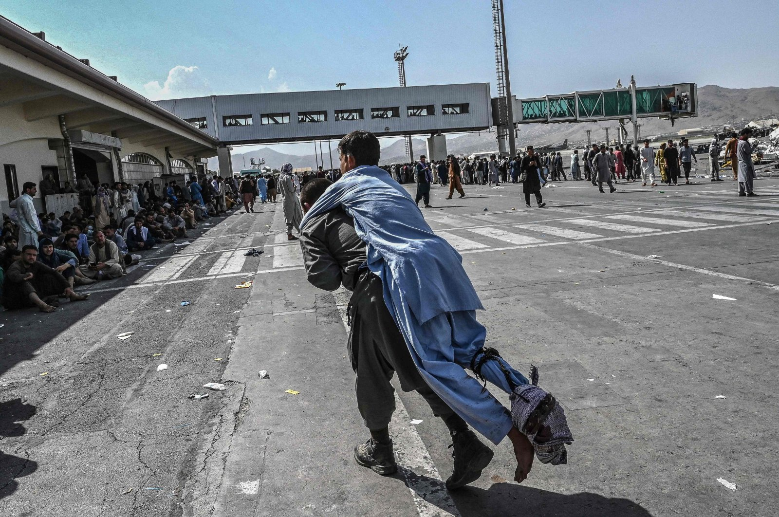 A volunteer carries an injured man as other people can be seen waiting at the Kabul Hamid Karzai International Airport, Kabul, Afghanistan, Aug. 16, 2021. (AFP Photo)