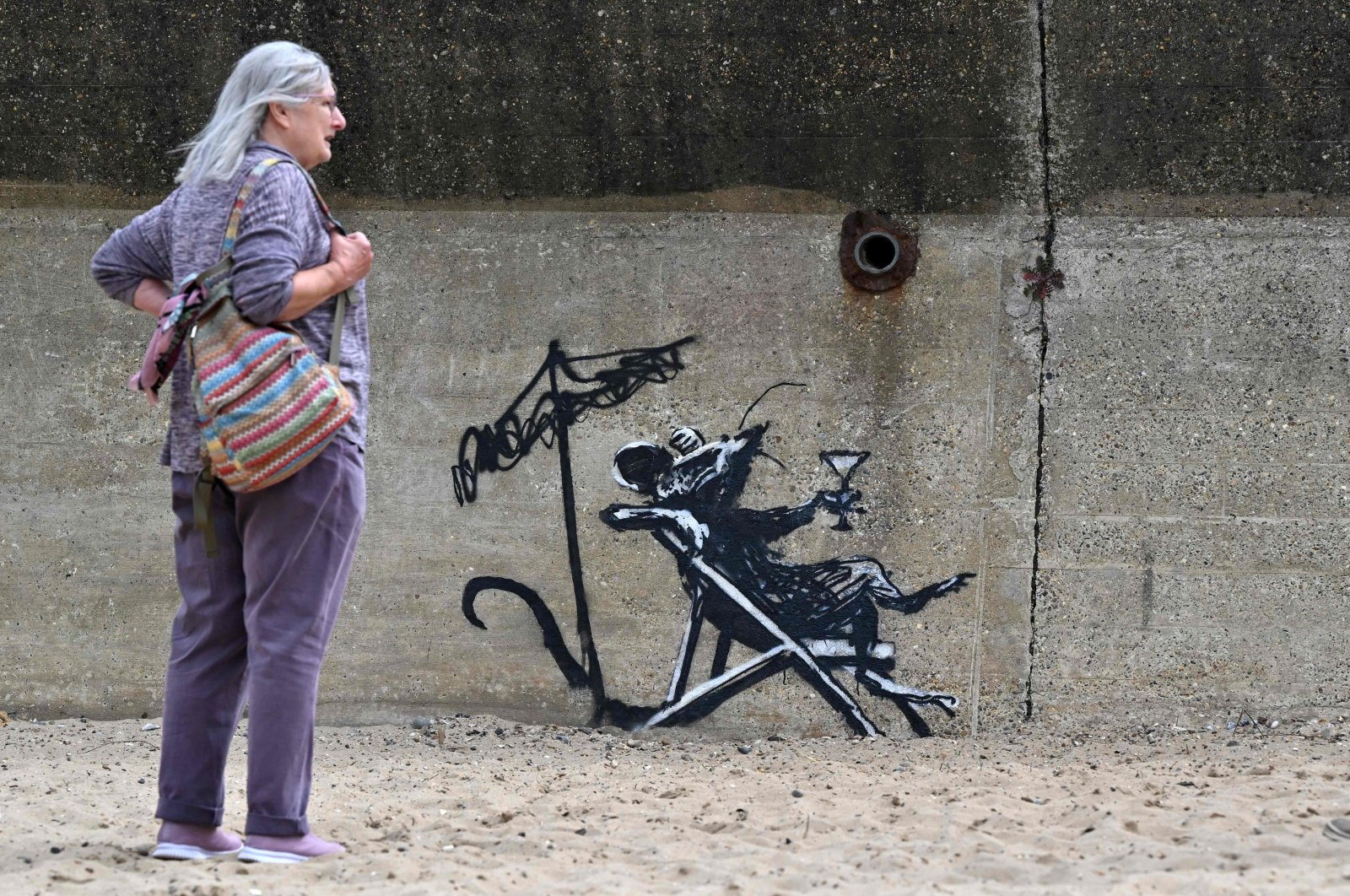 A woman stands beside a graffiti artwork of a rat drinking a cocktail by artist Banksy on a wall at North Beach, Lowestoft, England, Aug. 8, 2021. (AFP Photo)