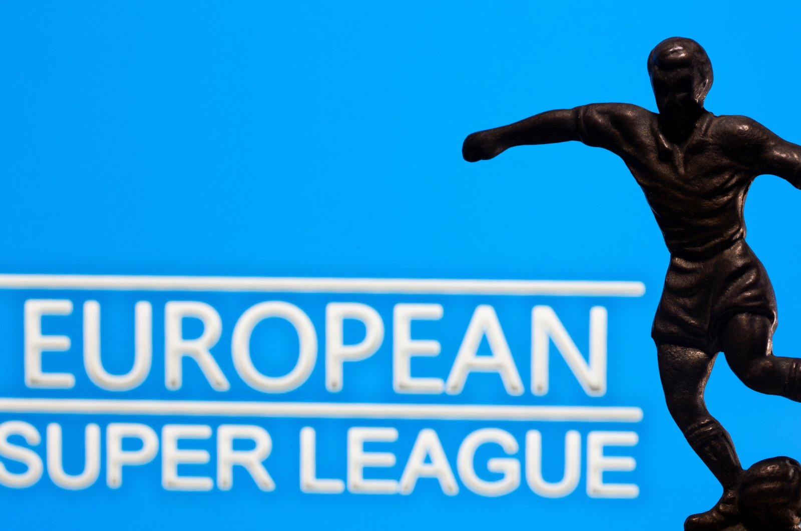 """A metal figure of a football player with a ball is seen in front of the words """"European Super League"""" in this illustration taken April 20, 2021. REUTERS/Dado Ruvic/Illustration"""