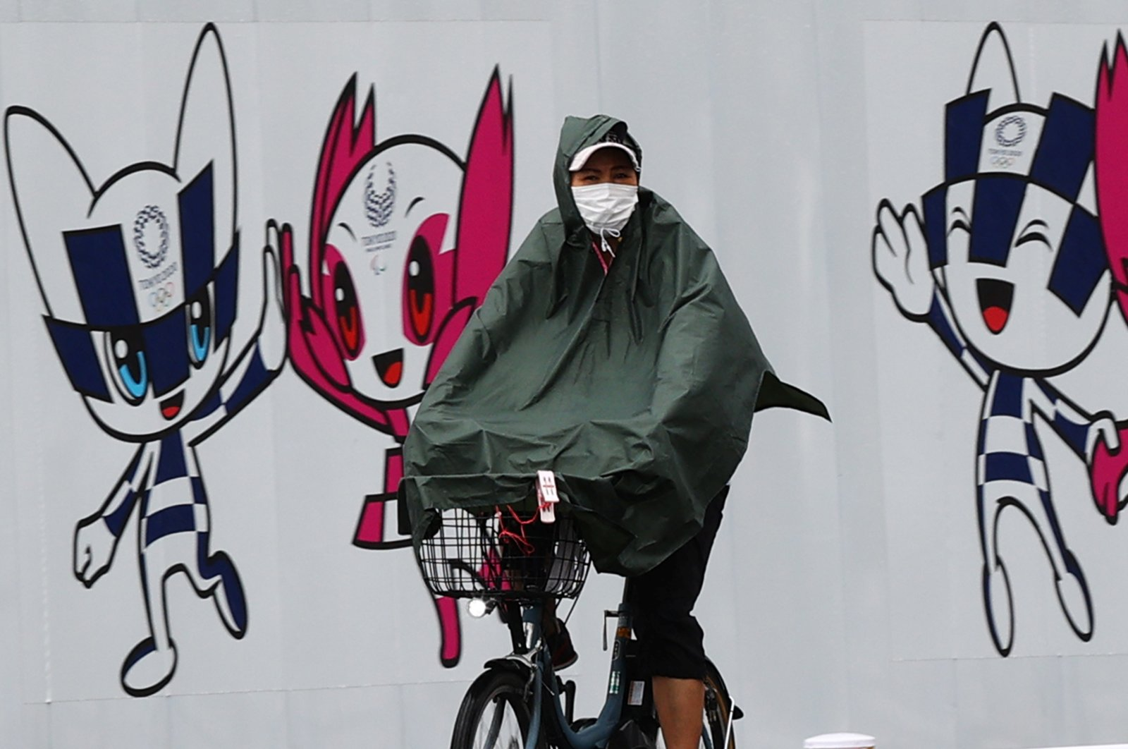 A person wearing a rain coat rides a bicycle in front of a wall decoration featuring Tokyo 2020 Olympic Games mascot Miraitowa and Paralympics mascot Someity, Tokyo, Japan, July 27, 2021. (Reuters Photo)