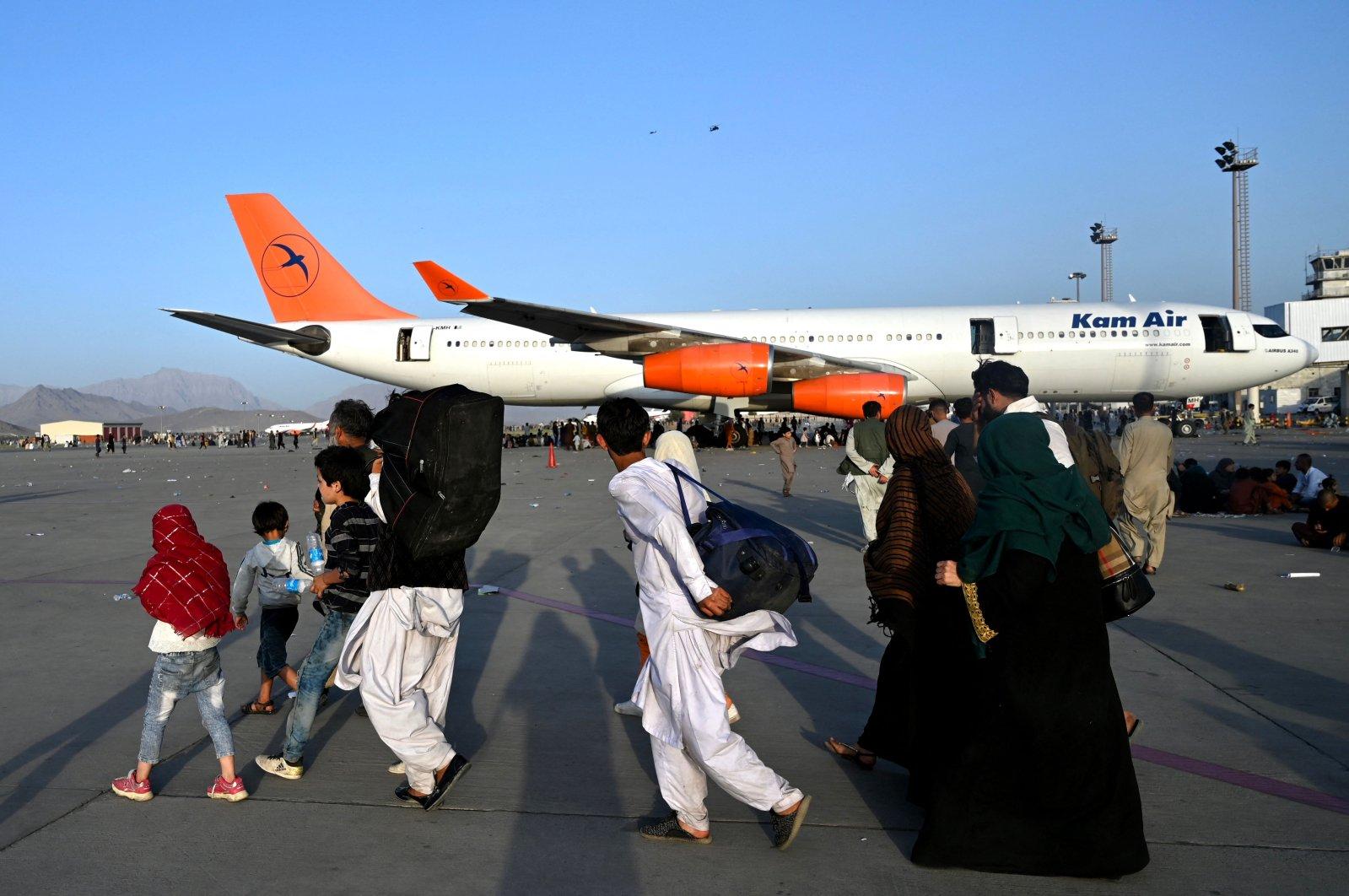 Afghan families walk by aircraft at Kabul Hamid Karzai International Airport, Kabul, Afghanistan, Aug. 16, 2021. (AFP Photo)