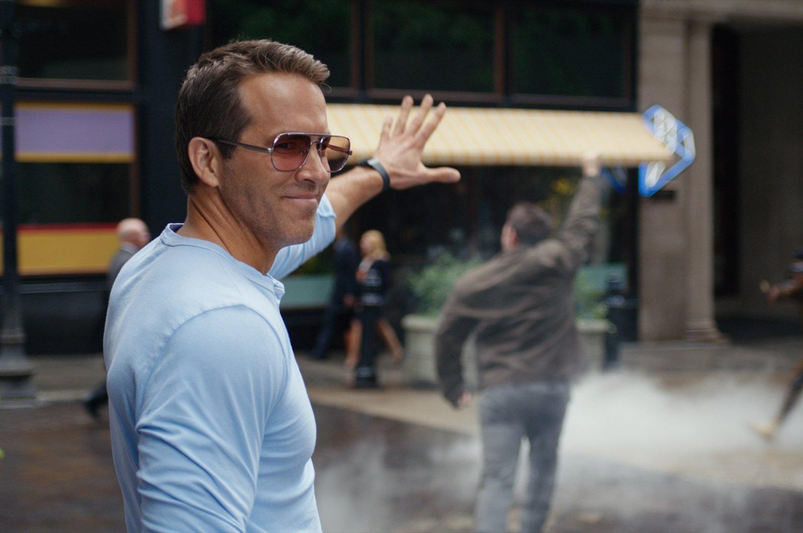 "Ryan Reynolds smiles in a scene from the film ""Free Guy."" (20th Century Studios via AP)"