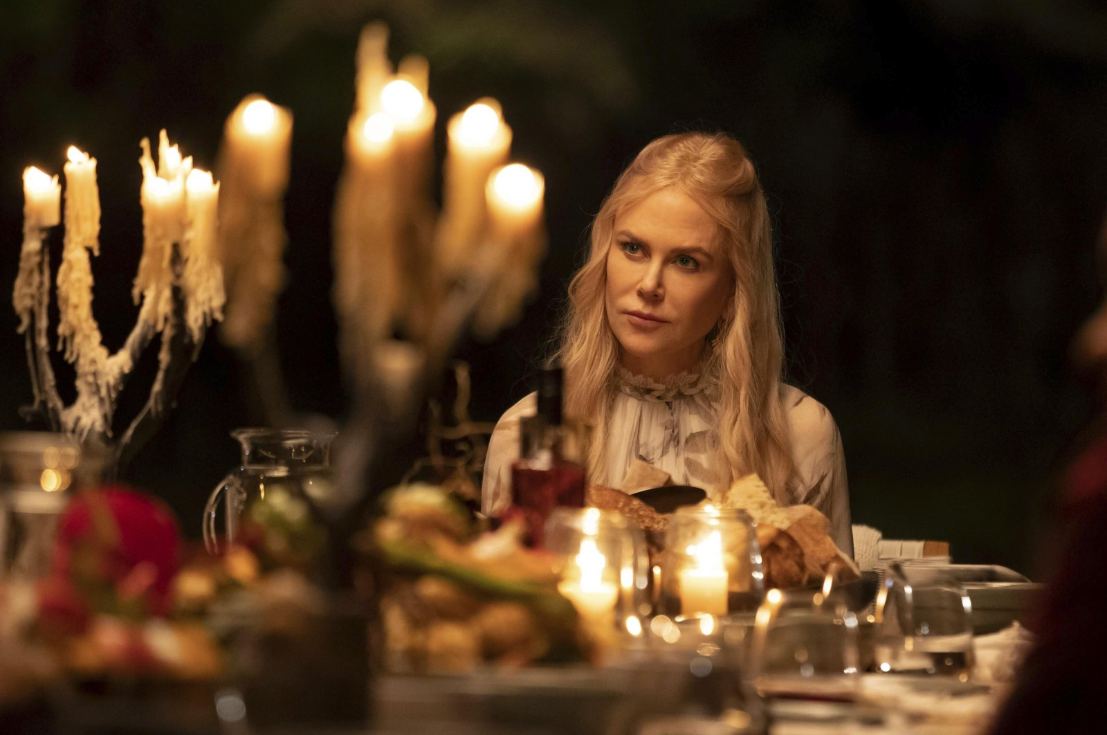 "Nicole Kidman sits on a table in a scene from the series""Nine Perfect Strangers,"" premiering Aug. 18 on Hulu. (Hulu via AP)"