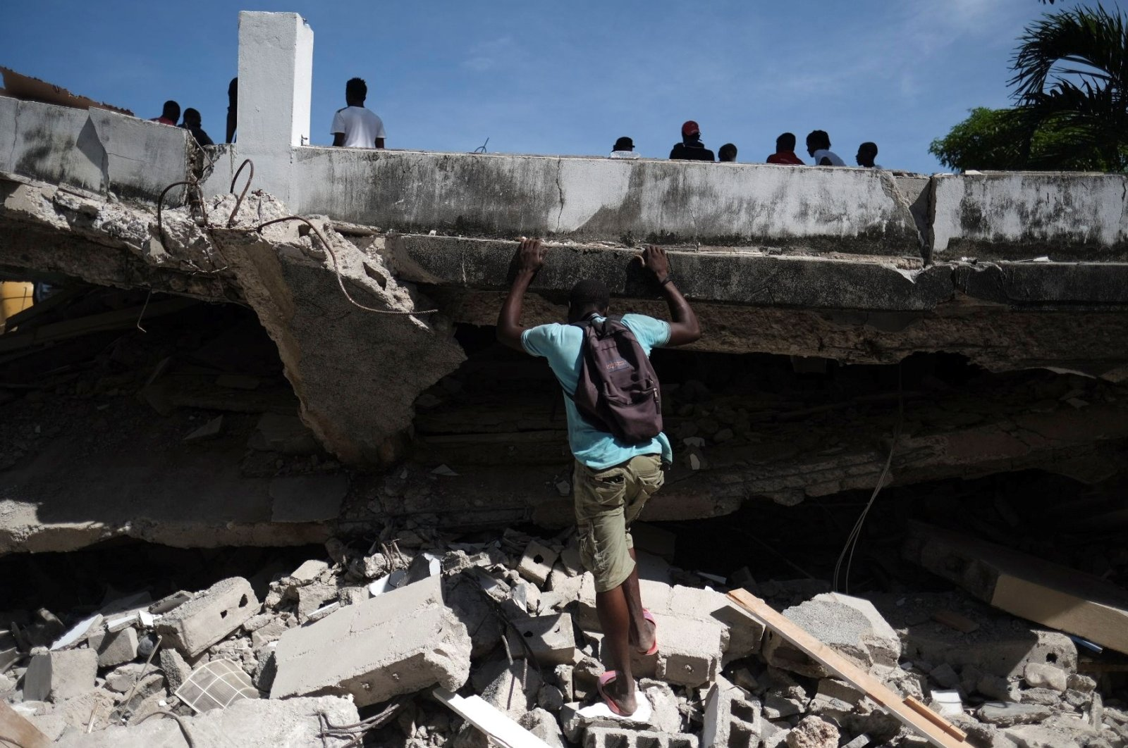 A man searches the site of a collapsed hotel after Saturday's 7.2 magnitude quake, in Les Cayes, Haiti, Aug. 16, 2021. (Reuters Photo)