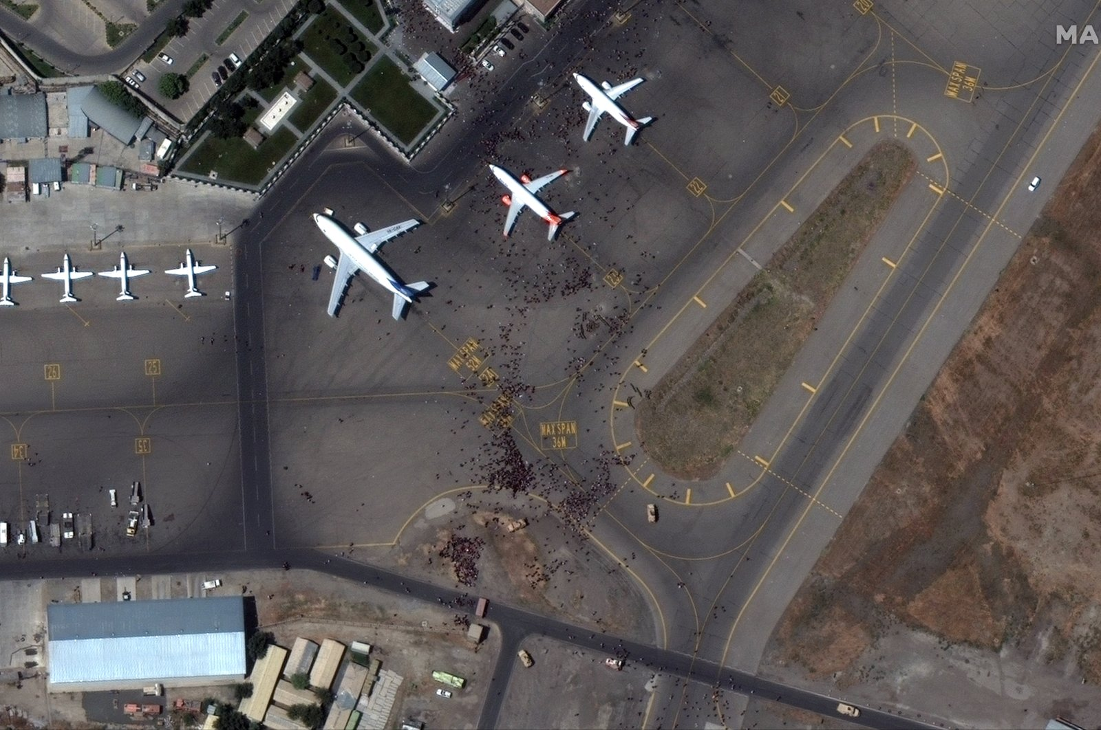 A handout satellite image made available by Maxar Technologies shows crowds on the tarmac of Kabul Hamid Karzai International Airport, Kabul, Afghanistan, Aug. 16, 2021. (Satellite image / 2021 Maxar Technologies via EPA)