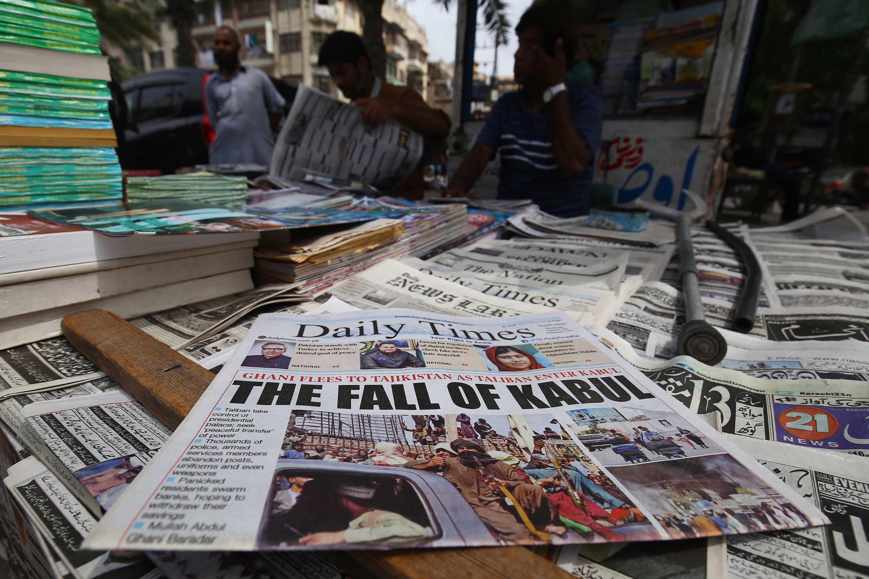 People read front-page news of the Taliban take over of Kabul, at a newspaper stall in Karachi, Pakistan, Aug. 16, 2021. (EPA Photo)