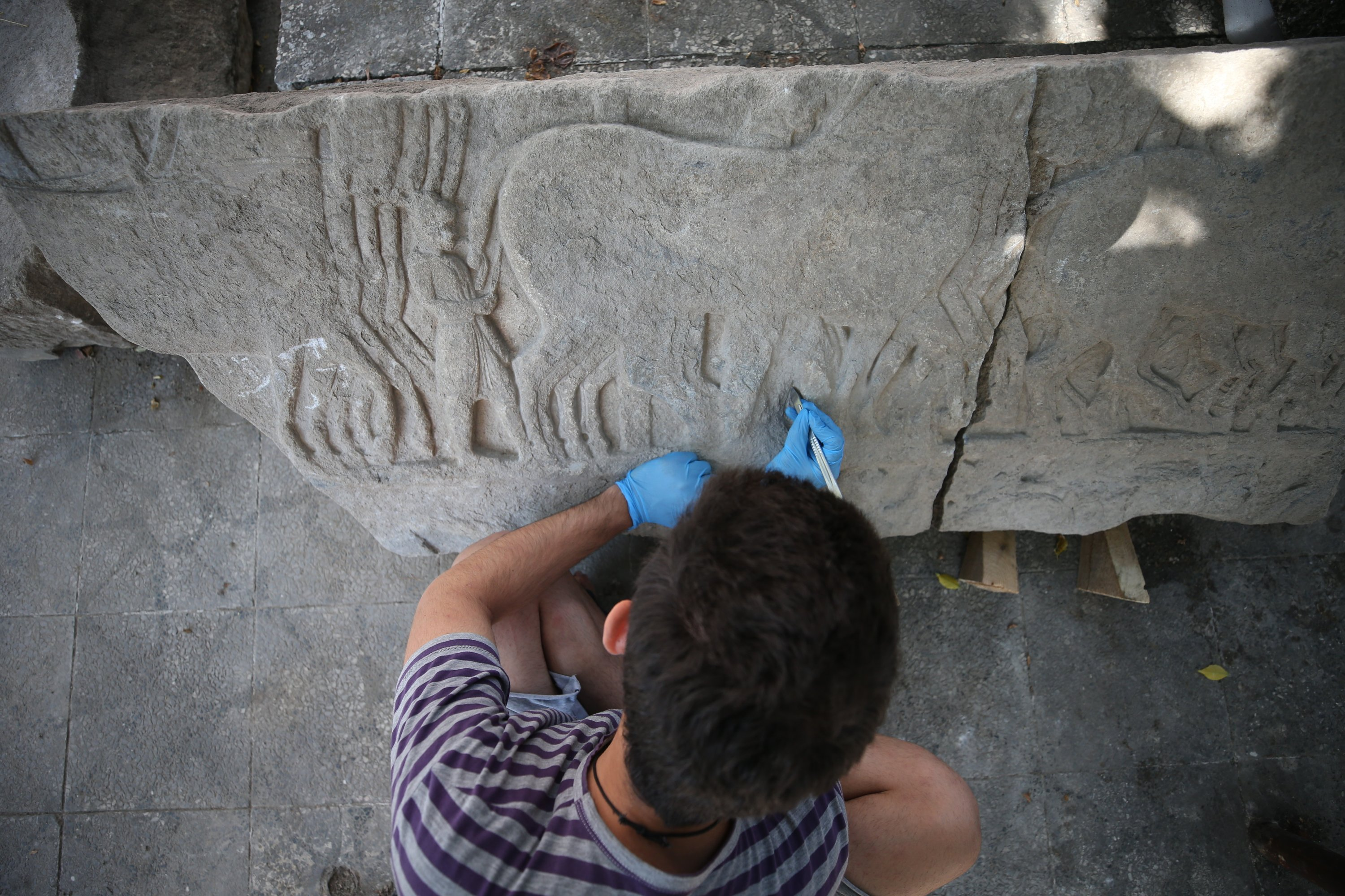 An archaeologist works on an ancient stone relief found in the ancient city of Daskyleion, Balıkesir, western Turkey, Aug. 16, 2021. (AA Photo)