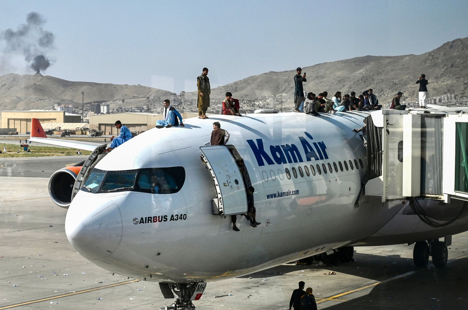 Afghan people climb on top of a plane as they attempt to flee the country after the Taliban entered the capital, at Kabul Hamid Karzai International Airport in Kabul, Afghanistan, Aug. 16, 2021. (AFP Photo)