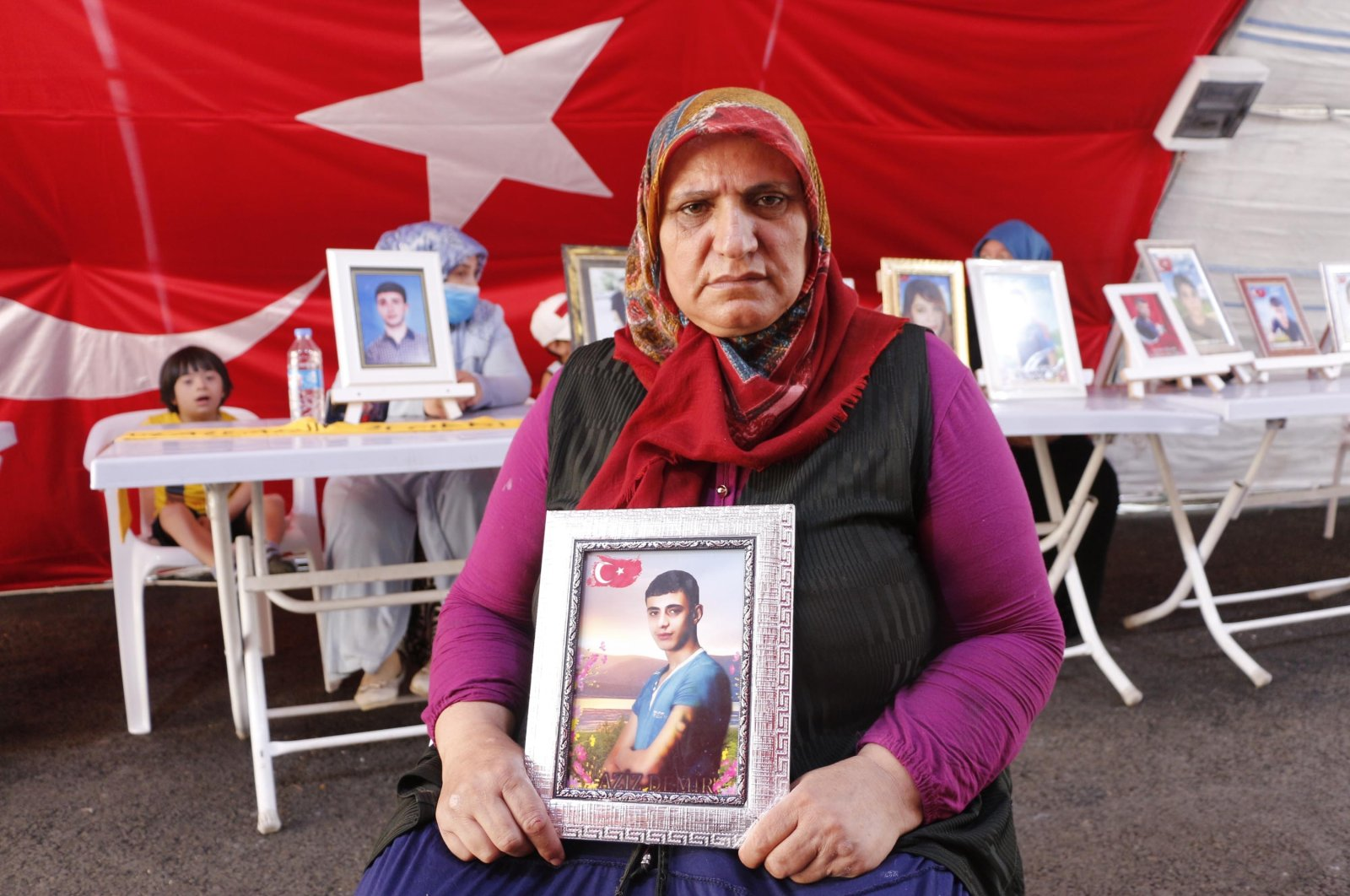 Güzide Demir holds a photo of her son, Aziz, in front of the HDP headquarters in southeastern Turkey, Aug. 5, 2021. (DHA File Photo)