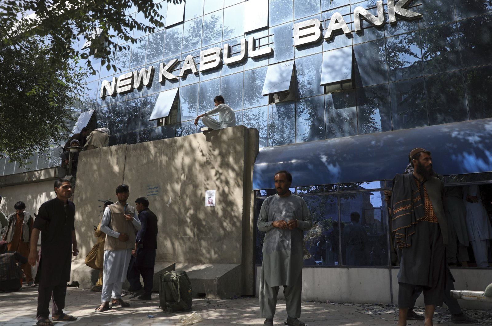 Afghans wait for hours to try to withdraw money, in front of Kabul Bank, in Kabul, Afghanistan, Aug. 15, 2021. (AP Photo)