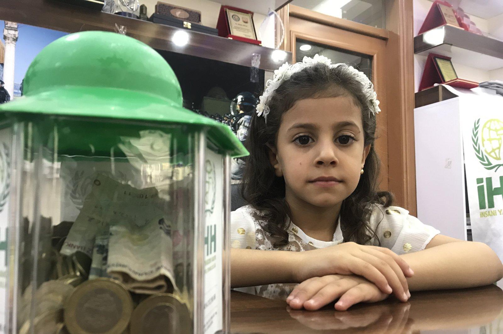 A Syrian orphan girl poses with her donation, in Şanlıurfa, southeastern Turkey, Aug. 16, 2021. (AA PHOTO)