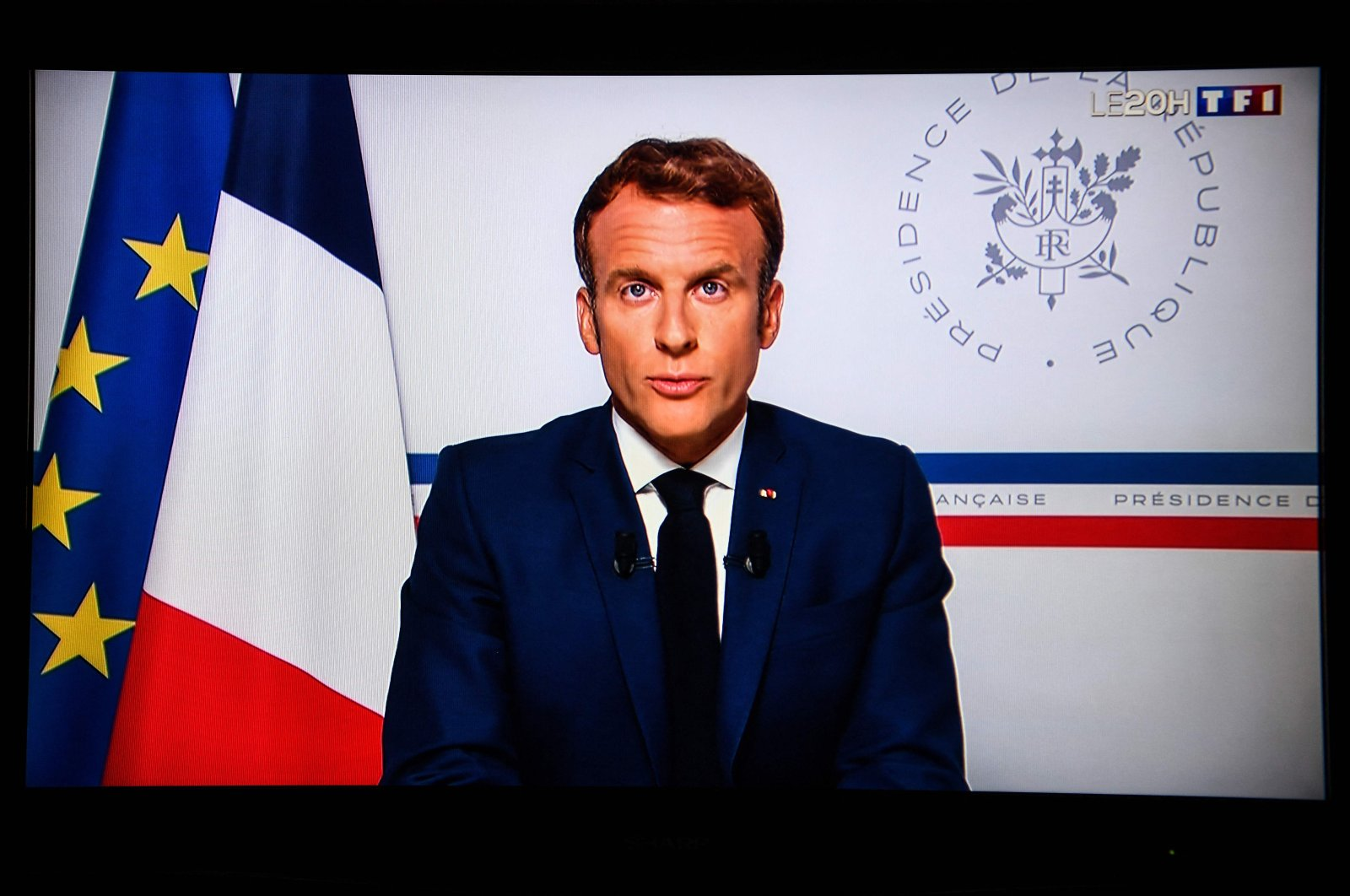 An image shot in Paris of a television screen shows French President Emmanuel Macron speaking on the situation in Afghanistan, from the Fort de Bregancon presidential summer residence at Bormes-les-Mimosas, southeastern France, Aug. 16, 2021. (AFP Photo)