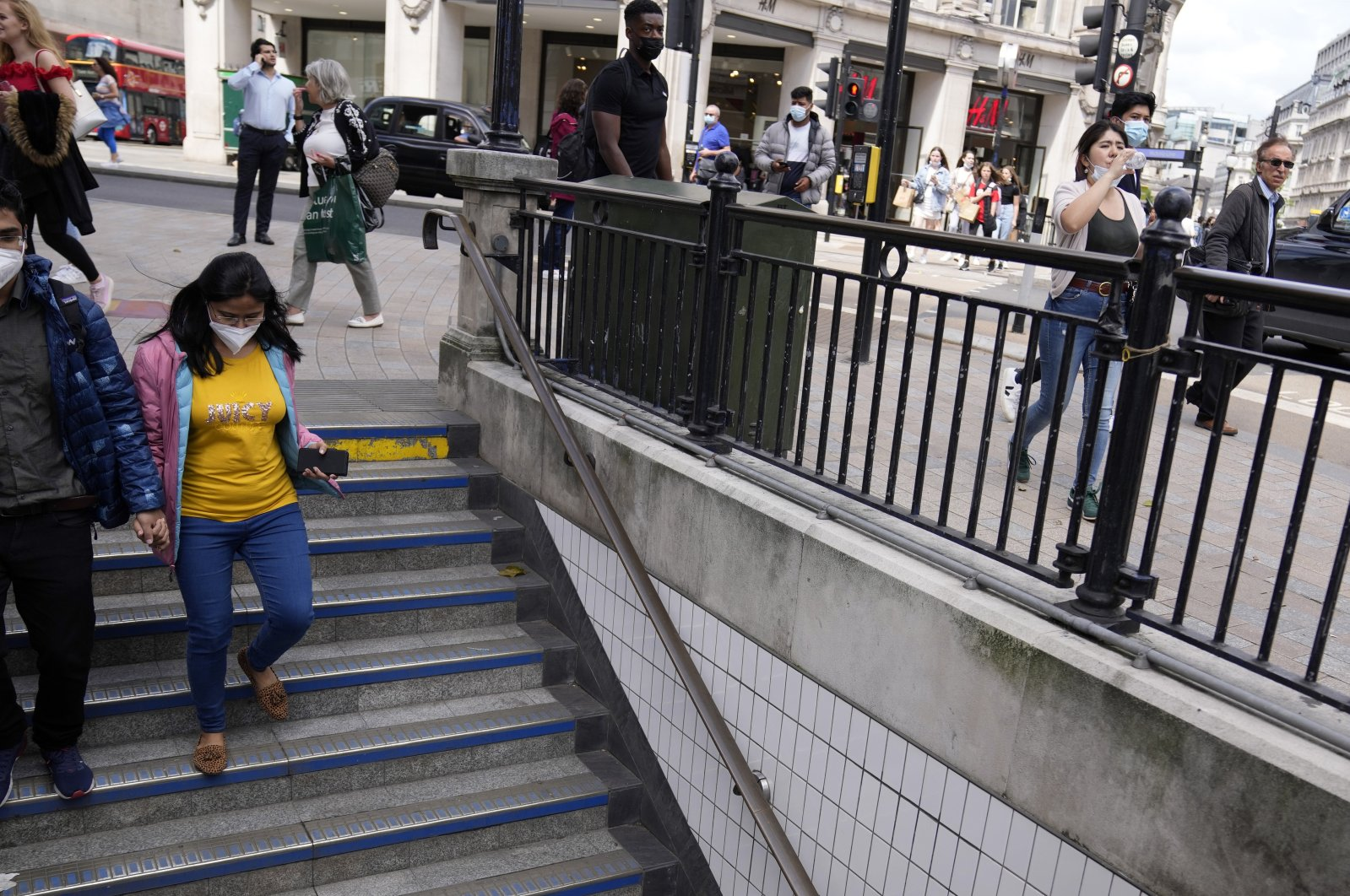 Pedestrians wearing face masks enter the Oxford Street tube station in London, Britain, Aug. 6, 2021. (AP Photo)