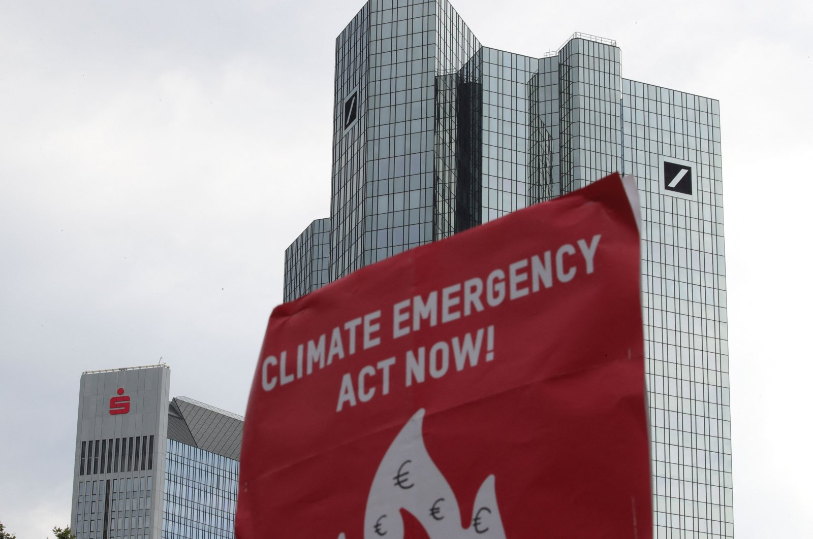 """A banner reading """"Climate emergency, act now"""" is pictured next to the headquarters of Deutsche Bank during a protest against bank investments in fossil fuels, in Frankfurt, western Germany, Aug. 13, 2021. (AFP Photo)"""