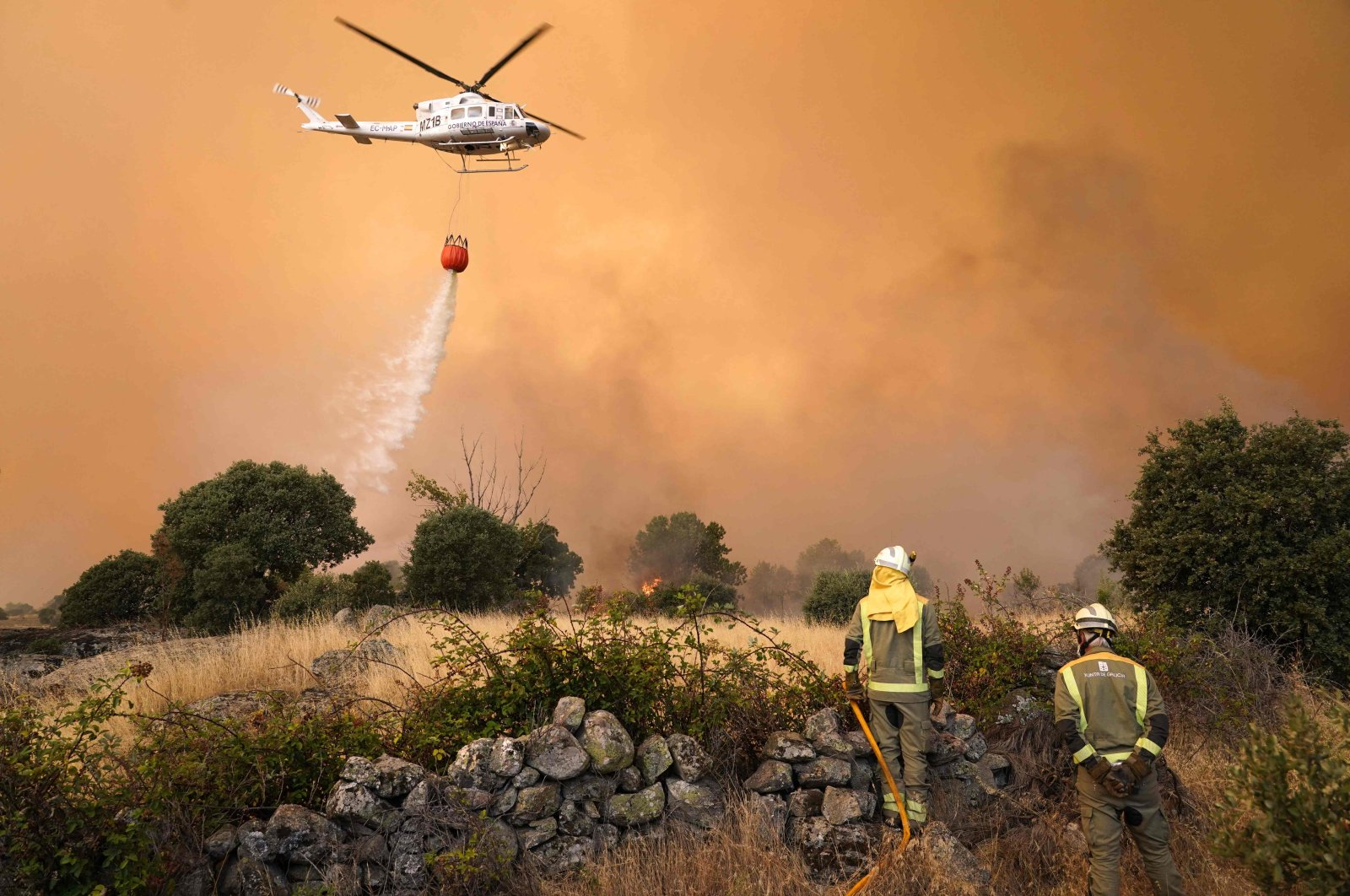 A helicopter drops water as fires rage in Navalmoral de la Sierra near Avila at the center of Spain on Aug. 16, 2021. (AFP Photo)