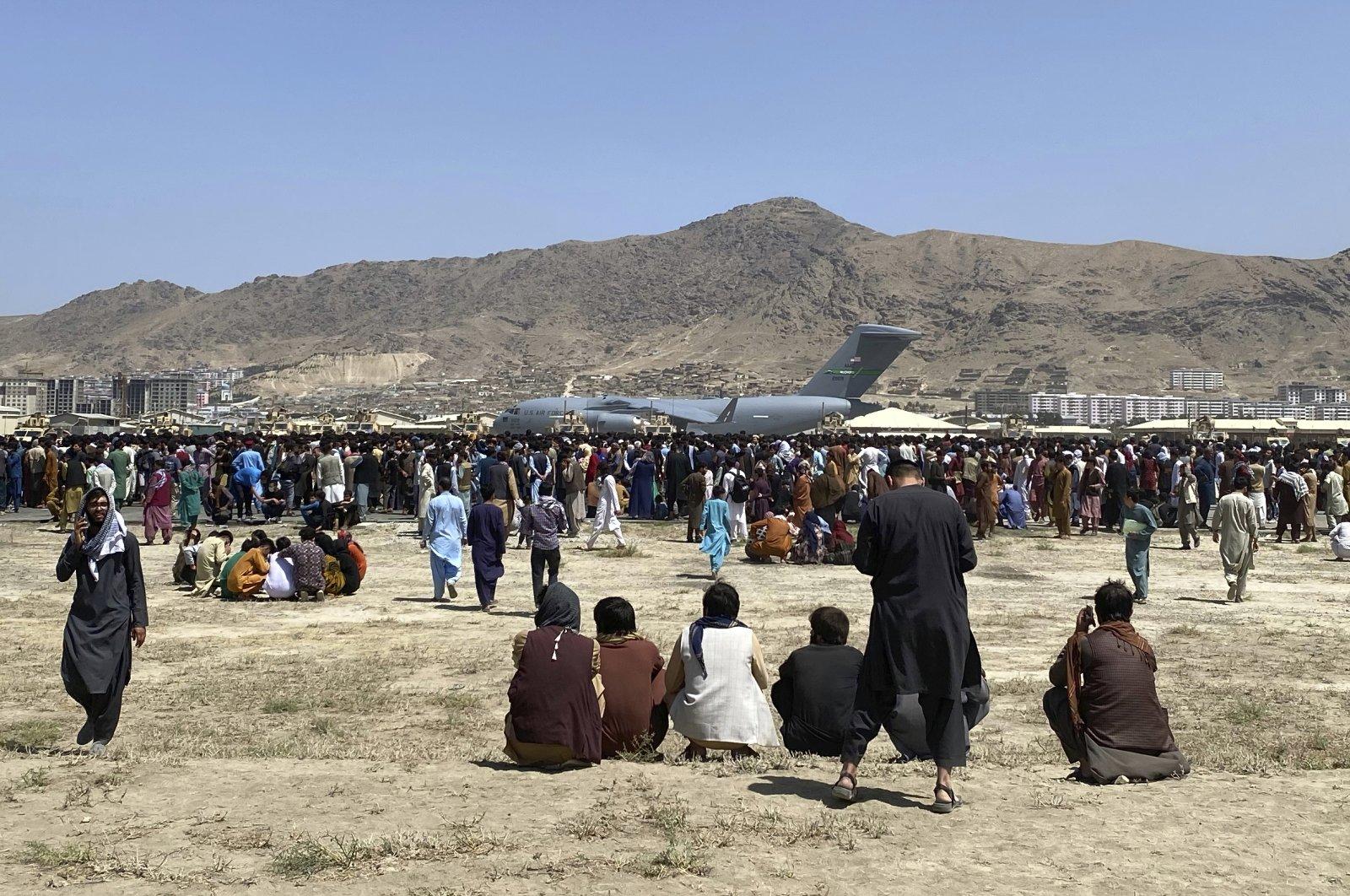 Hundreds of people gather near a U.S. Air Force C-17 transport plane at a perimeter at the international airport in Kabul, Afghanistan, Monday, Aug. 16, 2021. (AP Photo)