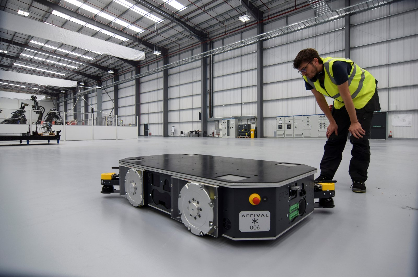 """An engineer at U.K. electric van and bus maker Arrival inspects a specially developed autonomous robot at the startup's low-cost """"microfactory"""" in Bicester, Britain, Aug. 3, 2021. (Reuters Photo)"""
