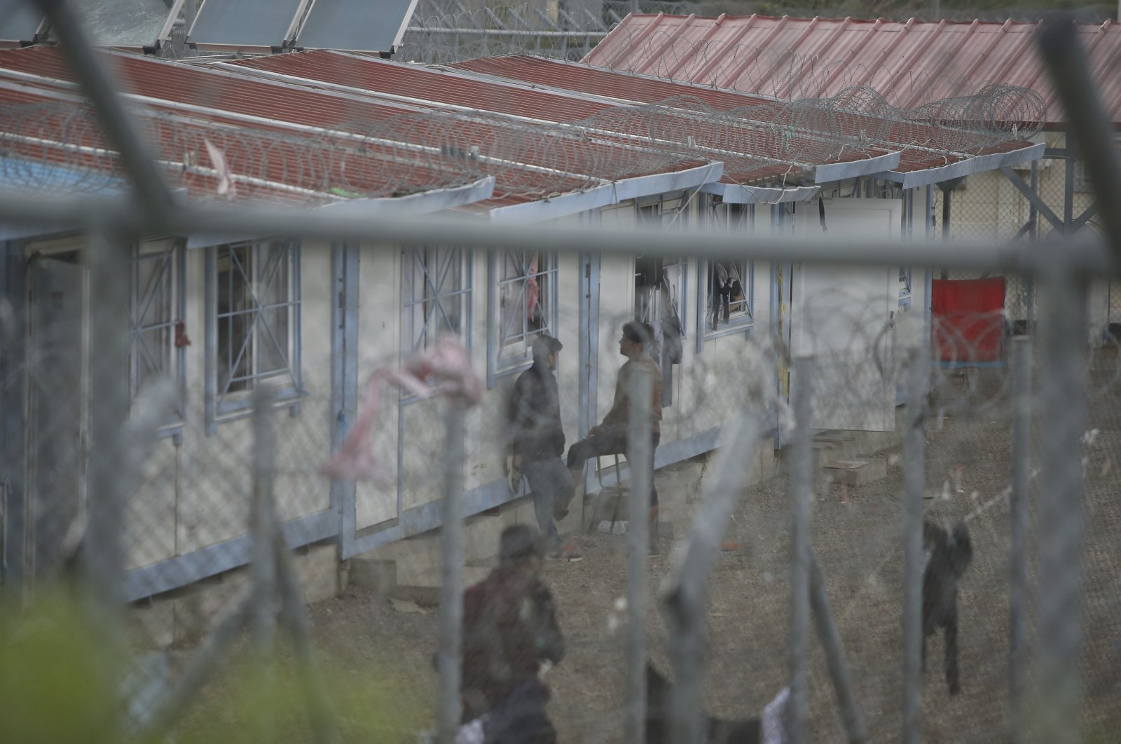 Migrants who were arrested after crossing illegally from Turkey to Greece stand behind a fence at a detention center near the village of Fylakio, at the Greek-Turkish border, Greece, May 21, 2021. (AP File Photo)