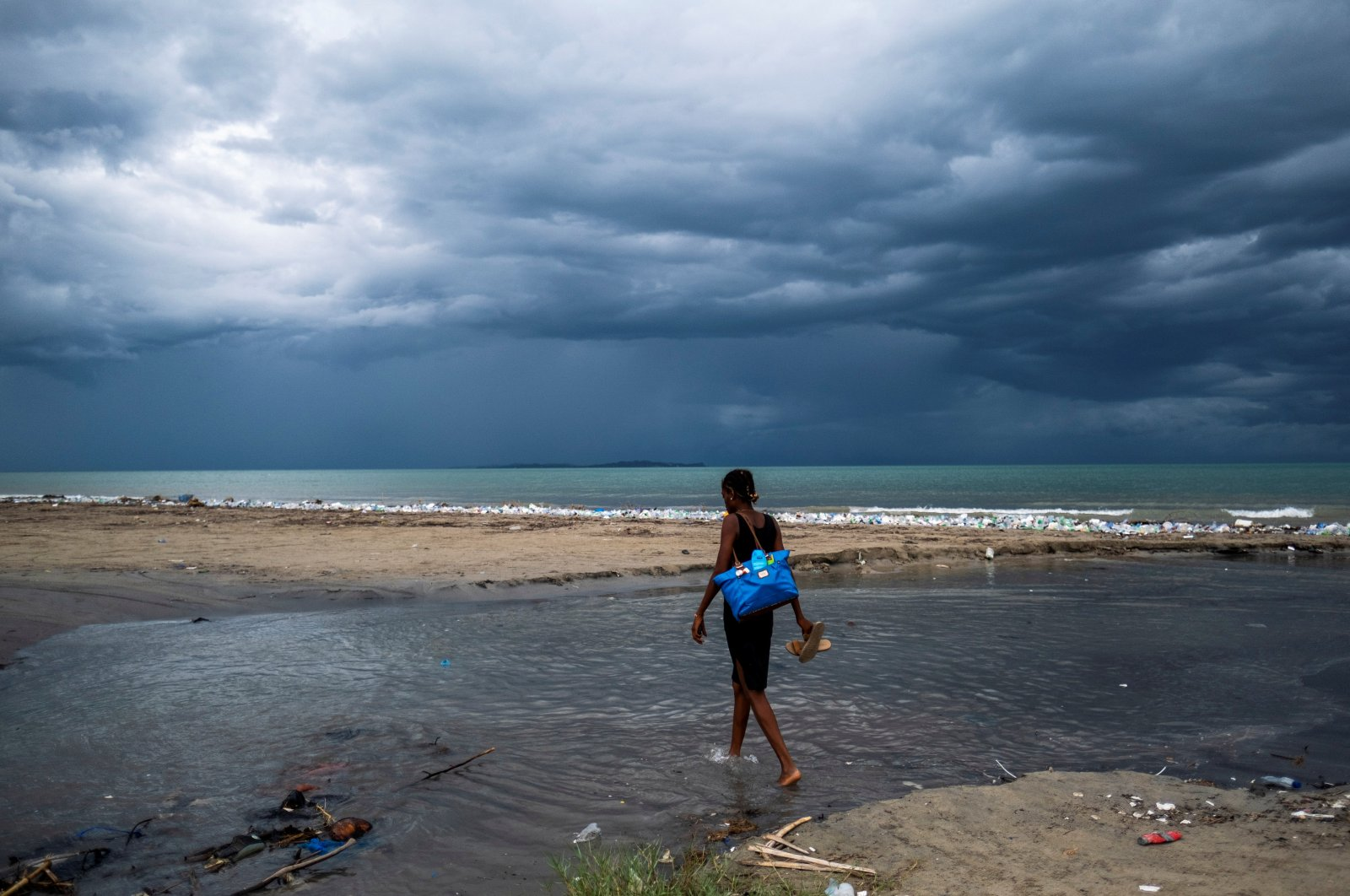 A woman wades through water as Tropical Depression Grace approaches, in Les Cayes, Haiti, Aug. 16, 2021. (Reuters Photo)